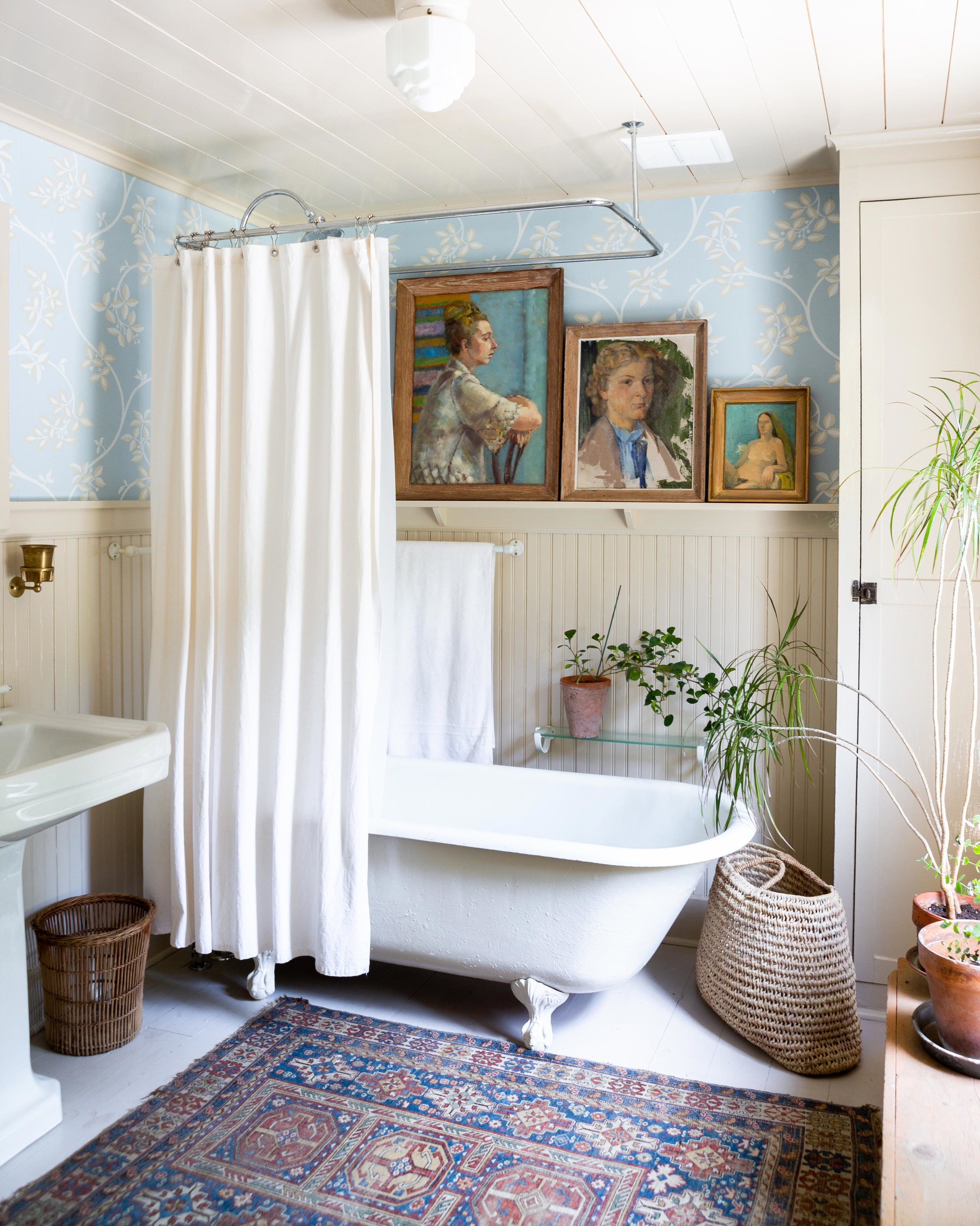 """The redesign of the cottage's bathroom began with an antique floor-to-ceiling cabinet that Prewitt and her husband """"found almost a year before we got the building,"""" she says. """"Drawing on it for inspiration, we sourced the other pieces, like the antique tub and the antique sink. Then I worked with Farrow & Ball, who supplied the wallpaper for me."""""""