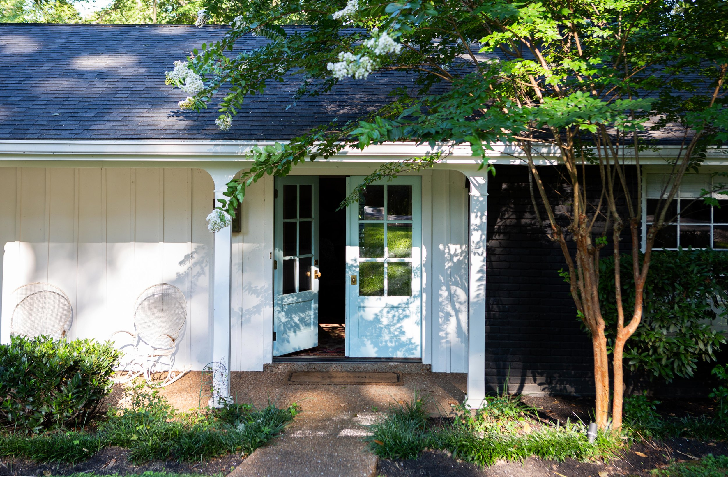 "The front of the lake house is where three contrasting exterior colors meet. The porch is painted white. The doors are powder blue. And the rest of the exterior is black. ""Some people like a sharp black-and-white house, but I didn't want it to be that stark and harsh,"" Colleen says. ""The blue adds the softness and charm that every welcoming entry needs."""