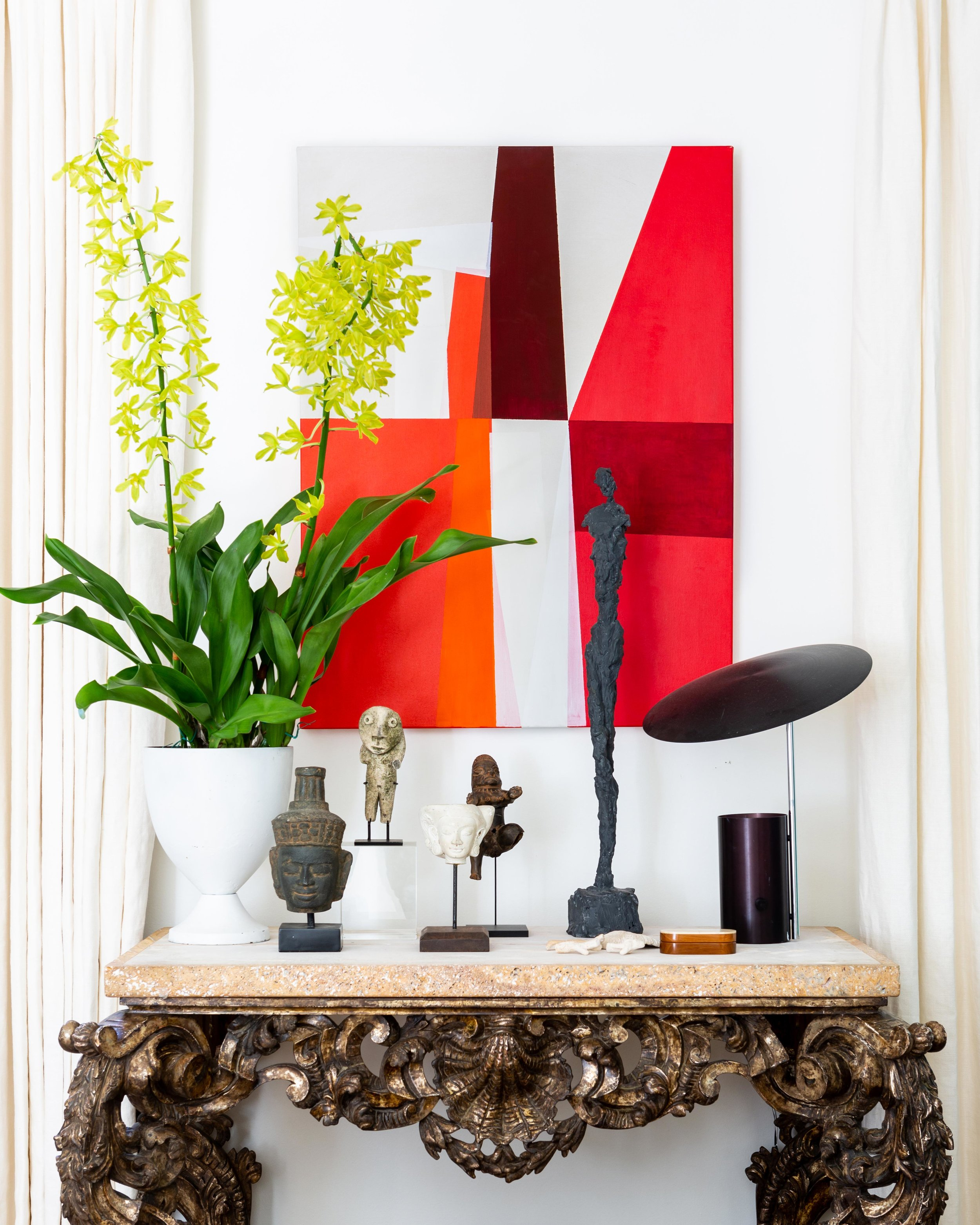 As a birthday present to himself, McLure bought this antique console from Interiors Market in Atlanta. A piece of abstract art by Catherine Booker Jones is displayed above it.