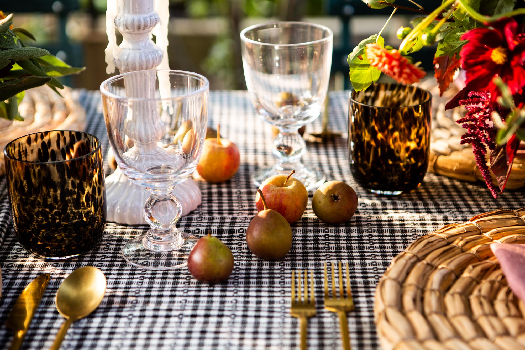 Dinner is about to be served: Sur La Table napkins and seagrass place mats top a Heather Taylor Home tablecloth; they're surrounded by Williams Sonoma wineglasses, and CB2 tortoiseshell tumblers and gold flatware.