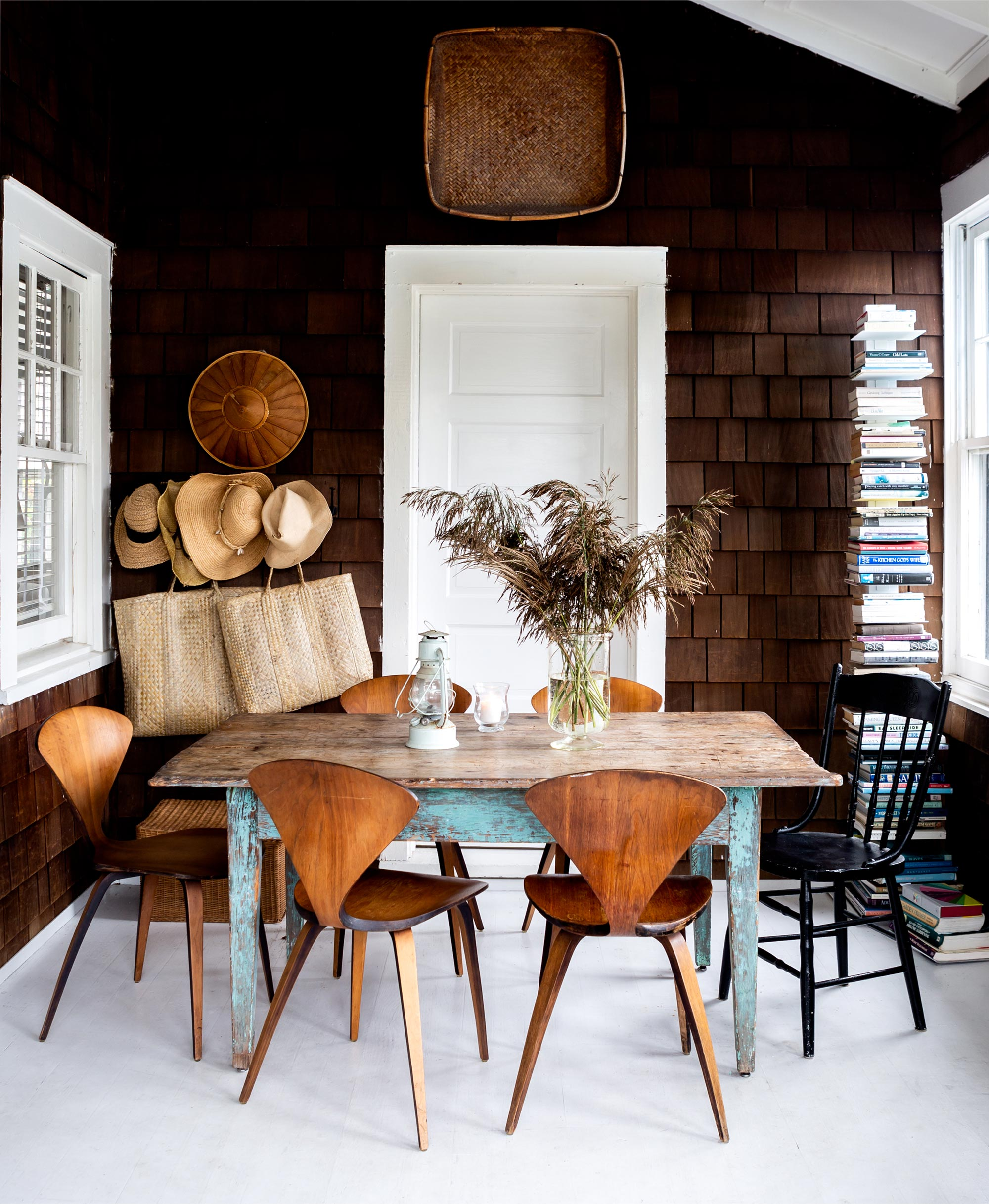"""Underlining the links between different design eras, Bates often pairs up unlike pieces, such as a well-used antique dining table and a midcentury set of Norman Cherner chairs. """"I've always loved American primitive furniture like that table because the lines do have this very clean, modern feeling to them, even though the pieces are actually very old,"""" she says. """"The chairs I bought one by one on eBay. Cherner is one of my favorite designers. I just think the form is beyond elegant."""""""
