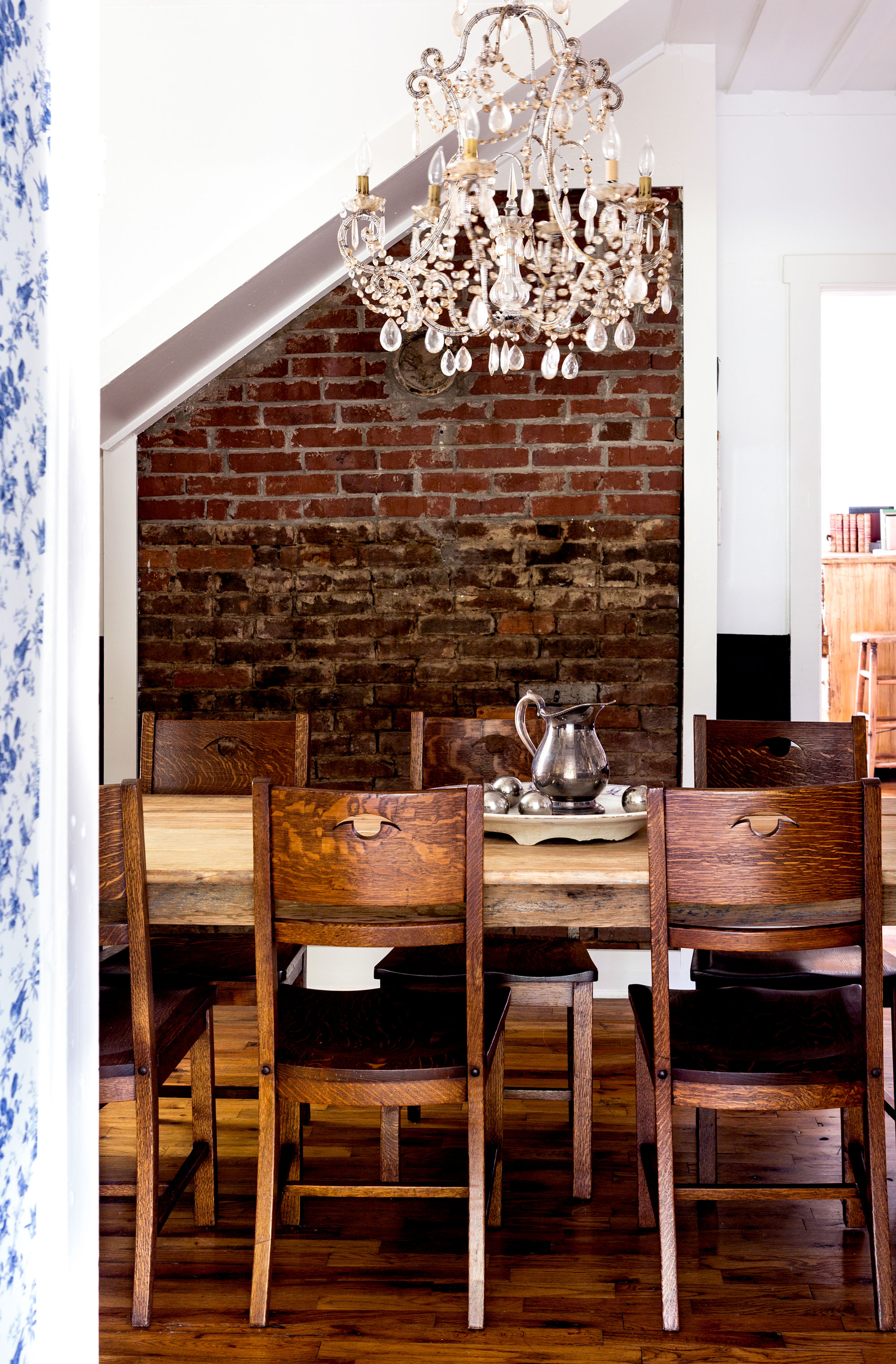 With Holly's found heirlooms on the walls, black beadboard paneling on white walls, a crystal chandelier, and a large farm table that easily seats eight, the cottage's dining room is relaxed enough for family cookouts and regal enough for Sunday dinners.