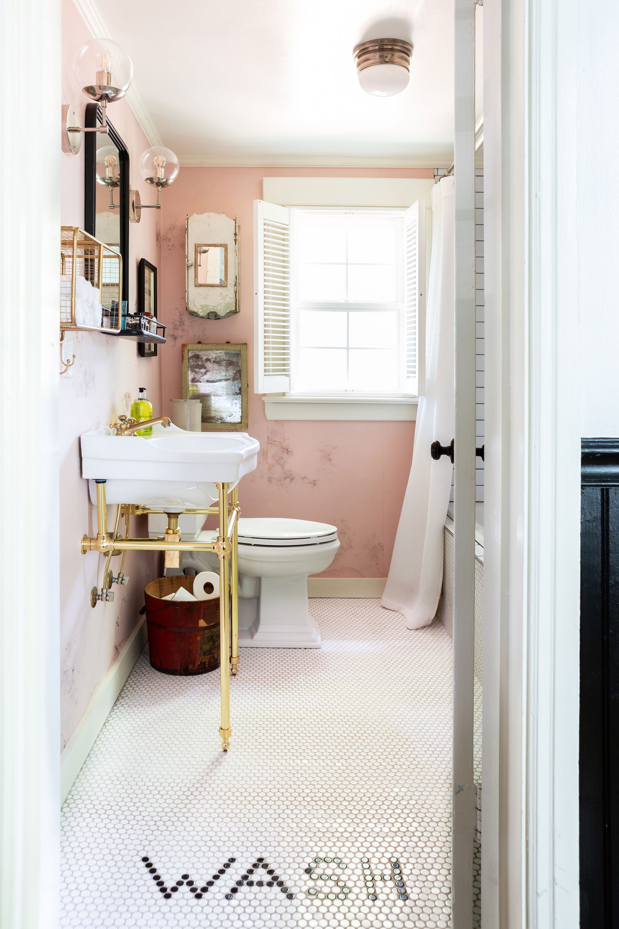 """""""No Southern home is complete without a stylish bathroom,"""" Holly says of her brassy, gold-on-pink design for the cottage's renovated water closet. """"There's absolutely got to be a soaking tub, too."""""""
