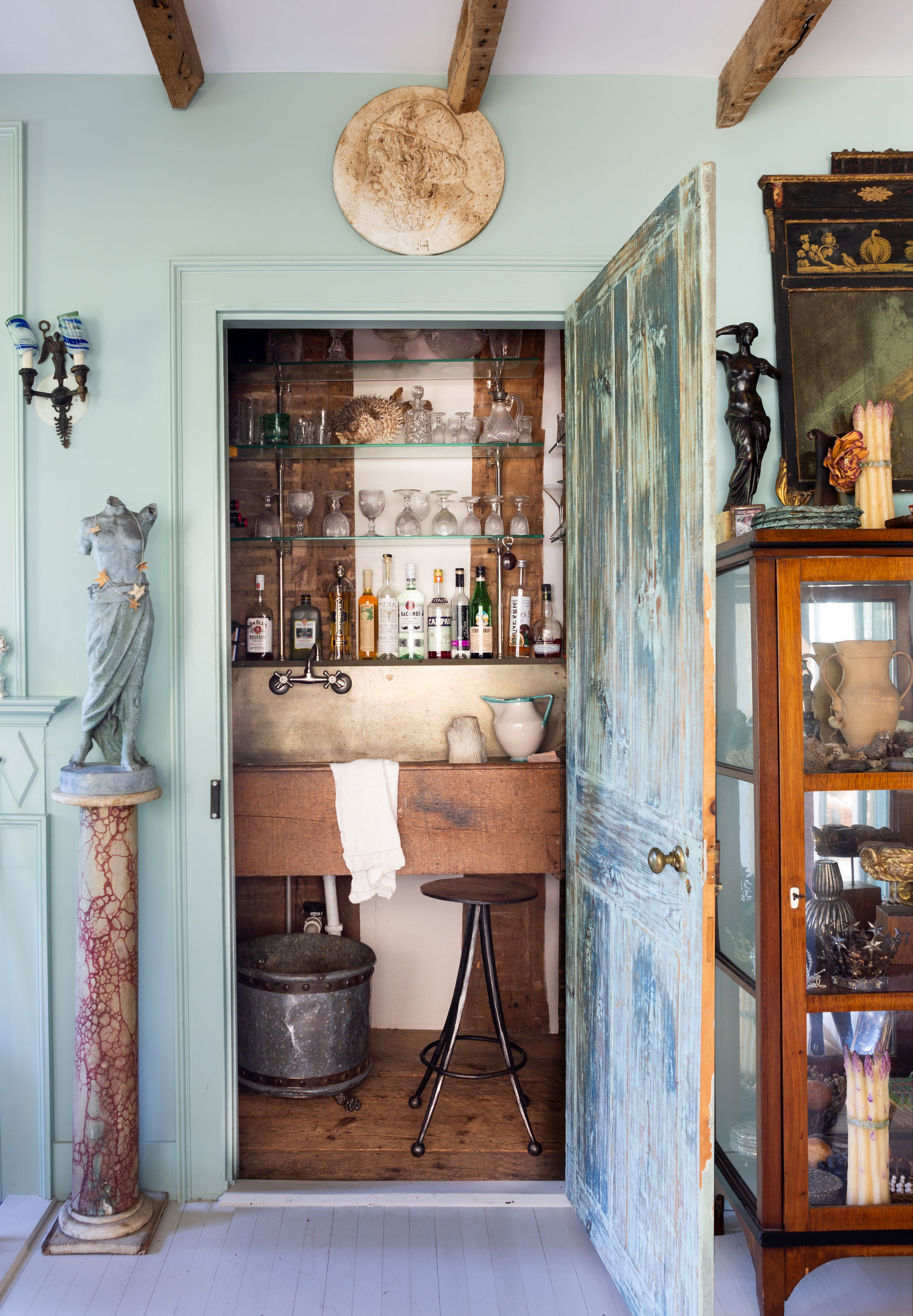 """A typically irreverent RT Facts touch: Natalie and Greg's little closet turned secret bar. """"It's pretty small, but it was really teeny before. We robbed space from a closet that was to the right of it,"""" Natalie explains. """"We love to wildly mix things, so it's got this old rustic wood-and-zinc bar sink, and then we've got these Deco shelves, along with all of these quirky things and an old bin that I gave iron feet to make it into a wastebasket. The door is usually closed. But when we have parties, we open it up. And it's nice to have a bar in a closet when you've got kids, because you can lock it,"""" she laughs."""