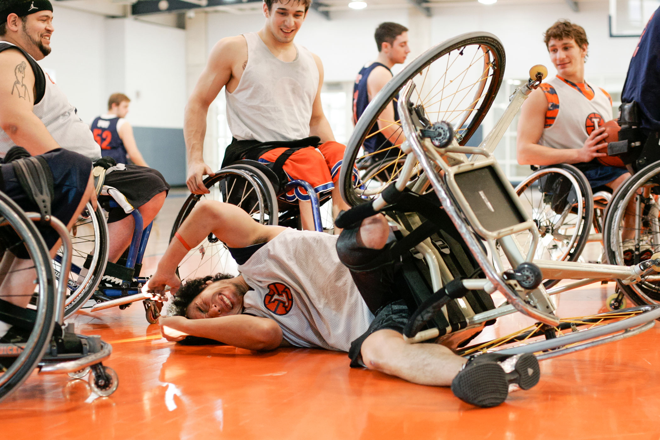 Wataru Horie, a player from Japan, grimaces and laughs with his teammates after falling over in his chair at practice. Frequently, players lose control of their chairs and fall, roll, or flip, but they can quickly push themselves up again and resume playing.