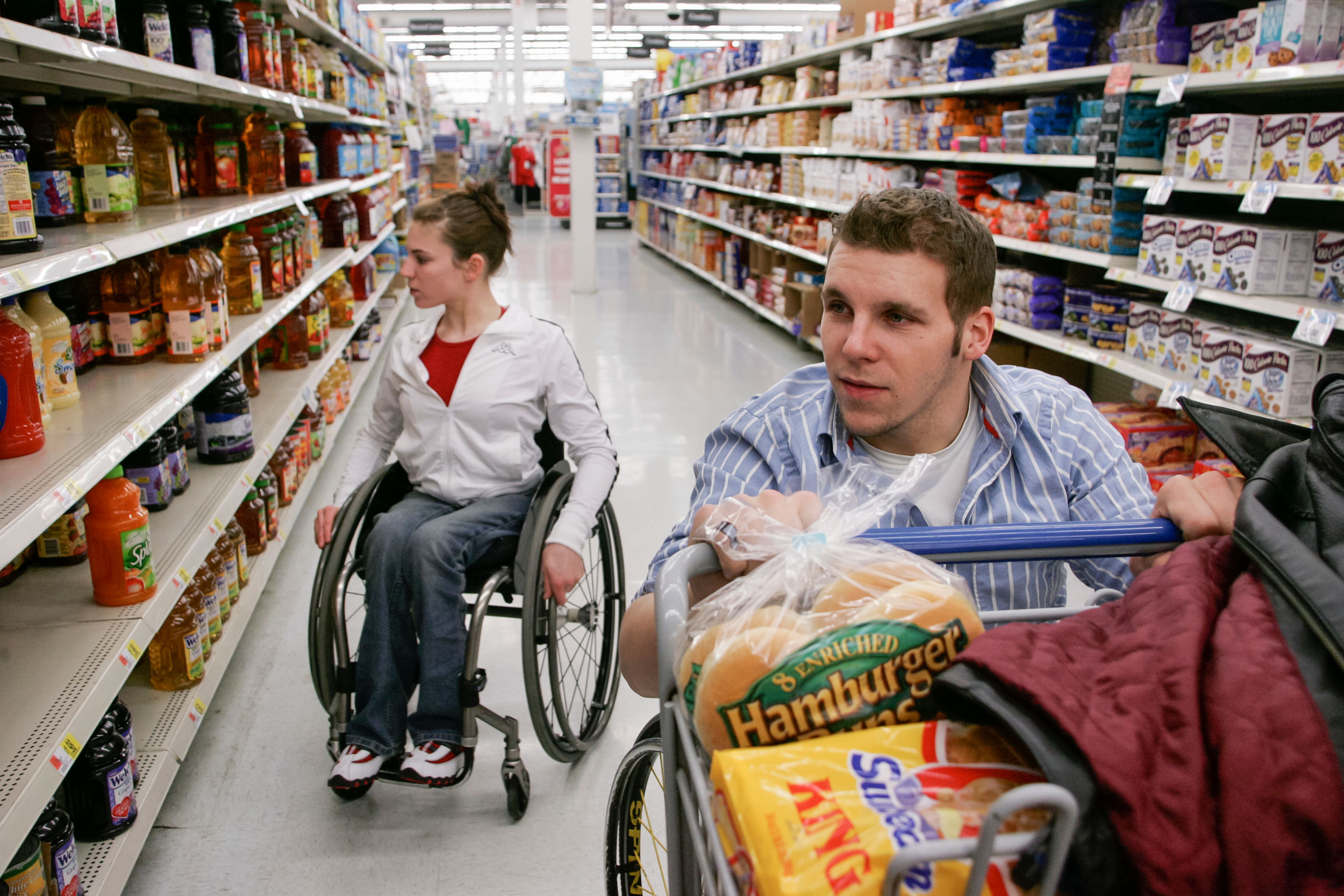 """Denny Muha and Amanda McGrory shop for food at Wal-Mart. Because Denny and Amanda are both in wheelchairs, """"it's easier to deal with any disability-related issues,"""" Muha said. """"I think it's easier because there's less to explain."""""""