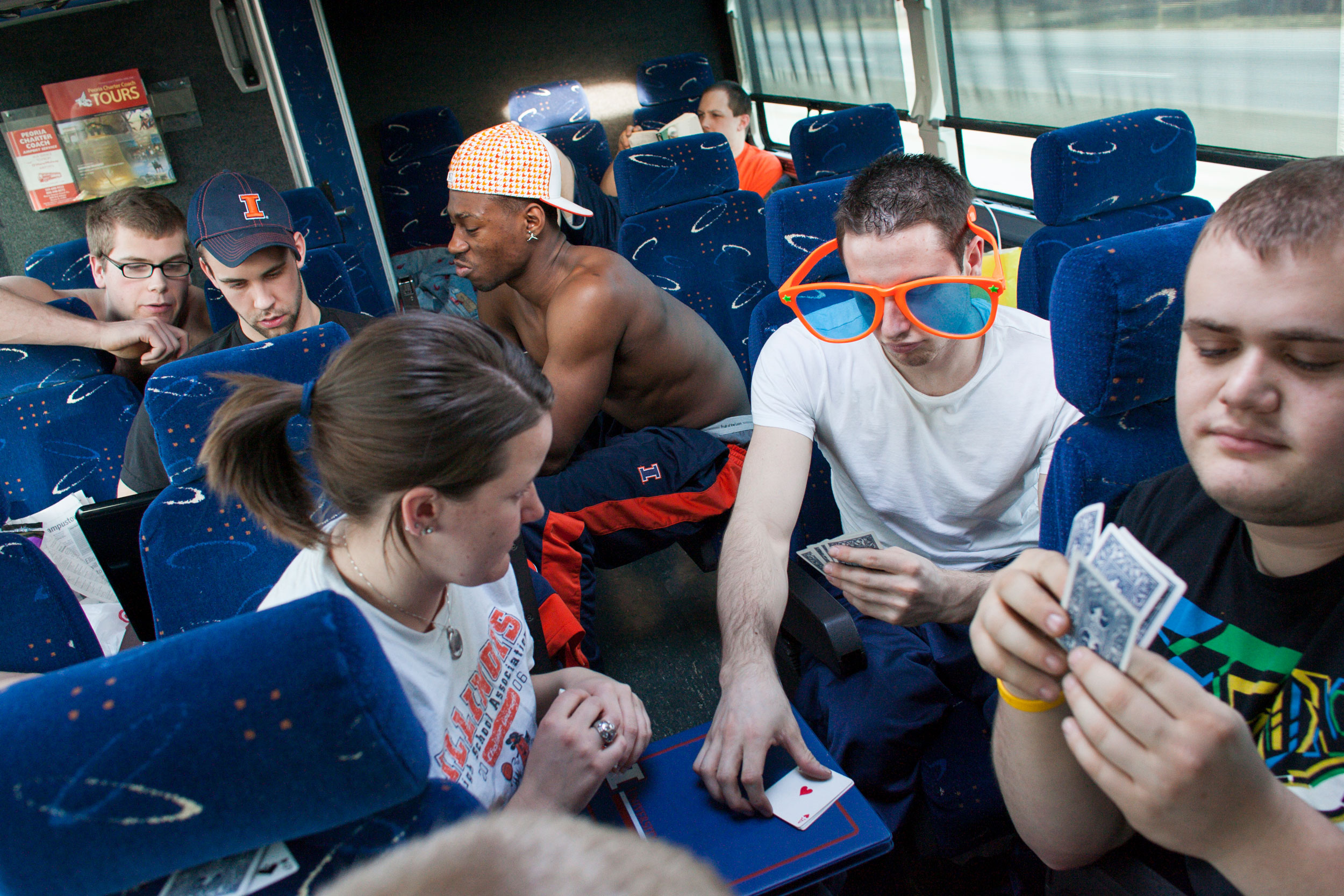 To ward off boredom on a bus trip, from right, Alex Grunstein, Steve Serio. and trainer Karla Wessels play cards; from left, Lars Spenger, Aaron Pike, and Brian Bell watch video on a laptop; and Drew Dokos, in the back, reads.