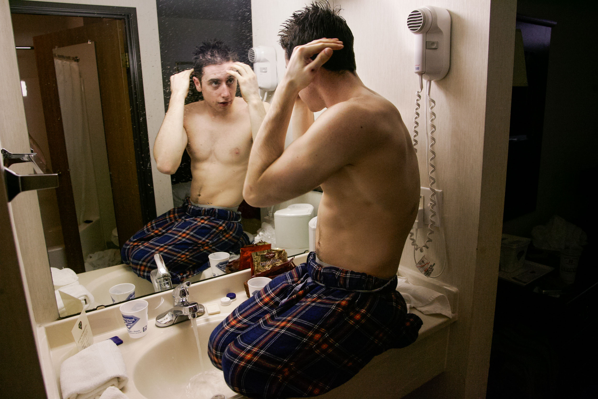 Steve Serio fixes his hair while sitting atop a counter at his hotel after a wheelchair basketball tournament.