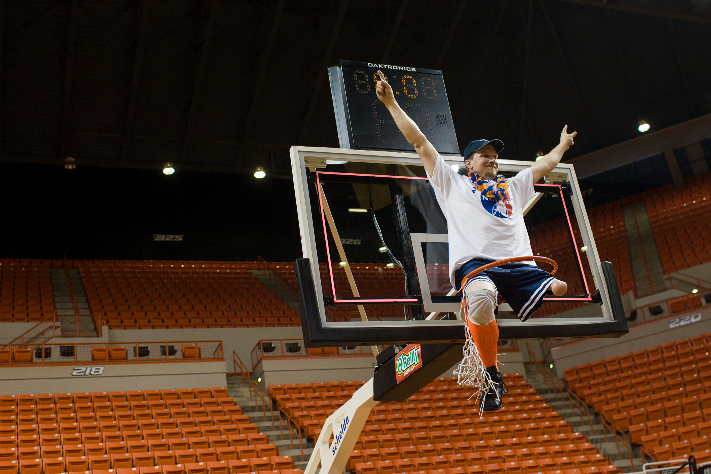 Drew Dokos celebrates the team's win atop the basket. The championship title was the first for the Illini men since 2001. It was also the first time since 1990 that both the Illini men and women have claimed titles.