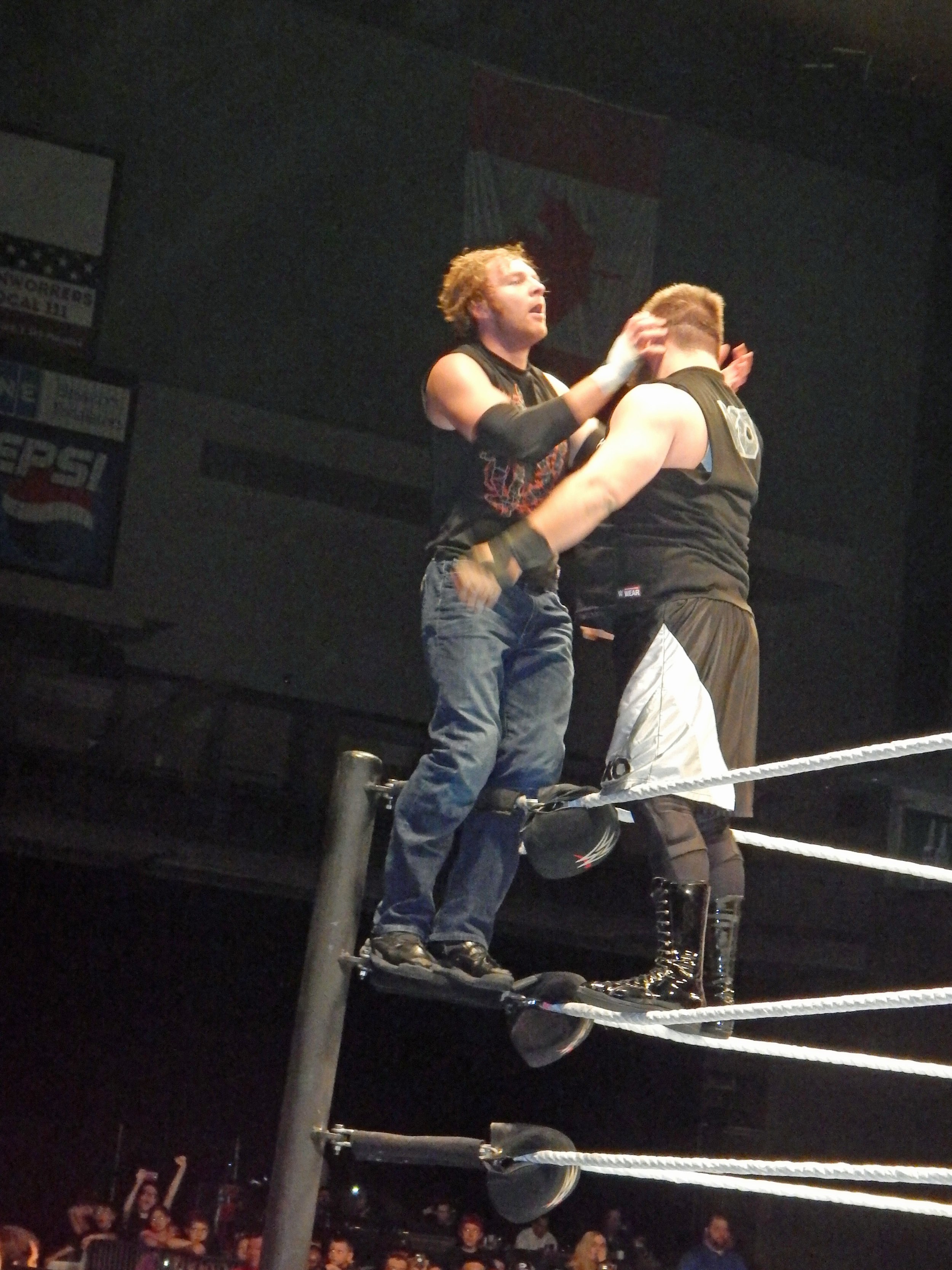 Dean Ambrose, left, stands on the second rope in the corner in a match against Kevin Owens at a WWE live event in Moline, Ill. on March 6, 2016. (Photo by Mike Pankow)