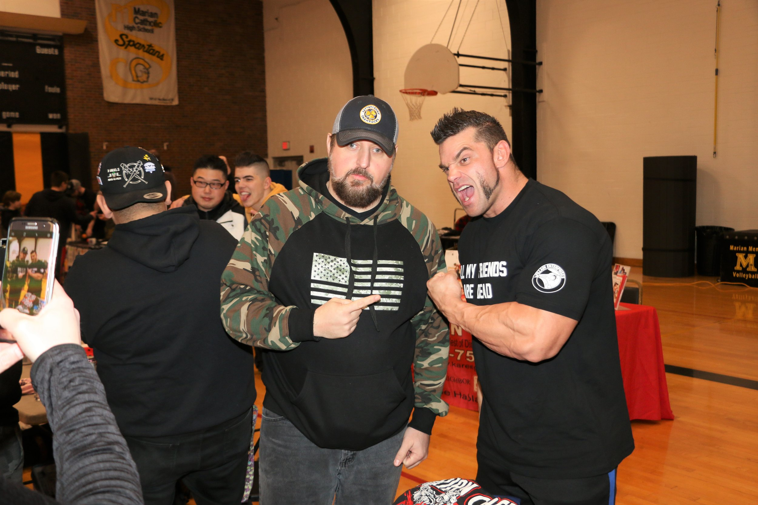 A fan poses with Warrior Wrestling Champion Brian Cage during the VIP Fan Fest.