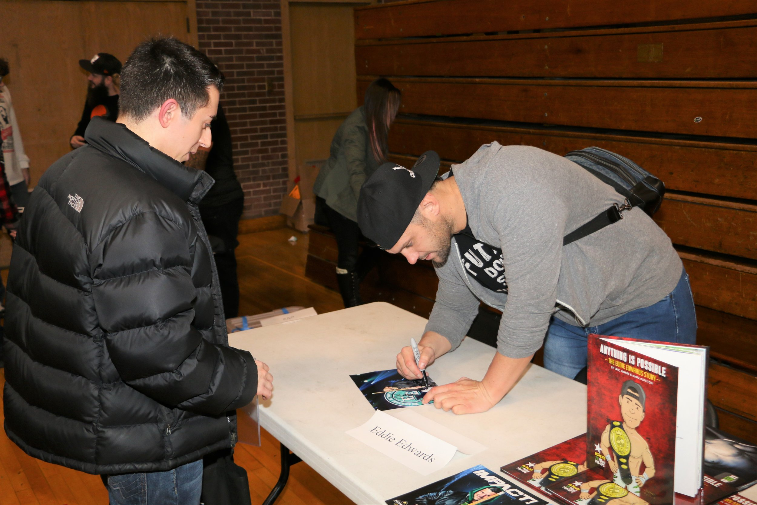 Eddie Edwards signs an autograph for a fan during the VIP Fan Fest.