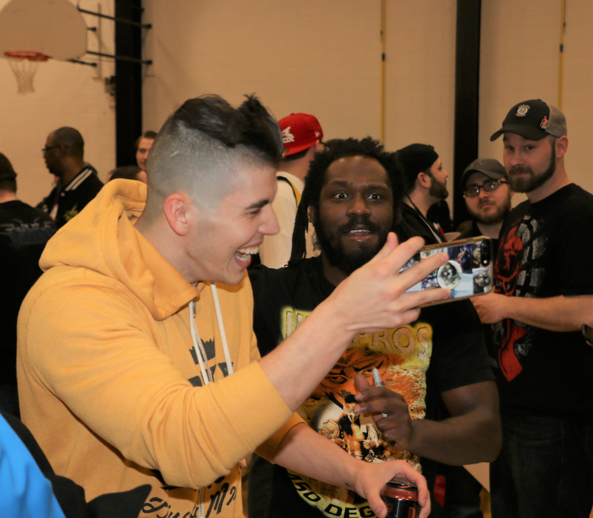 Sammy Guevara, left, and Rich Swann pose for selfies during the VIP Fan Fest.