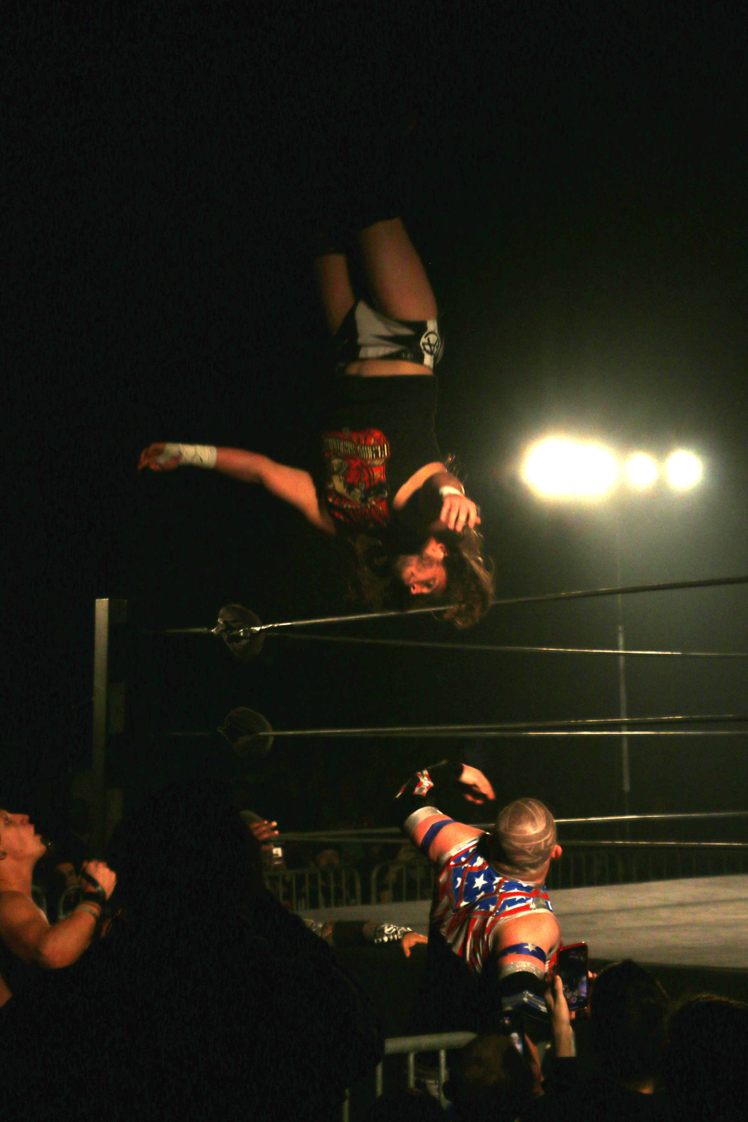 Andrew Everett moonsaults to the floor onto his opponents during the six-man scramble match.