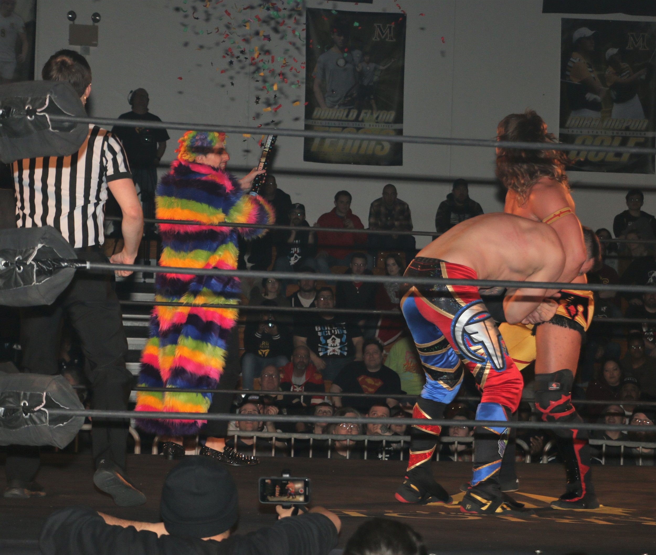 Frank the Clown distracts Brian Pillman Jr. from the ring apron.