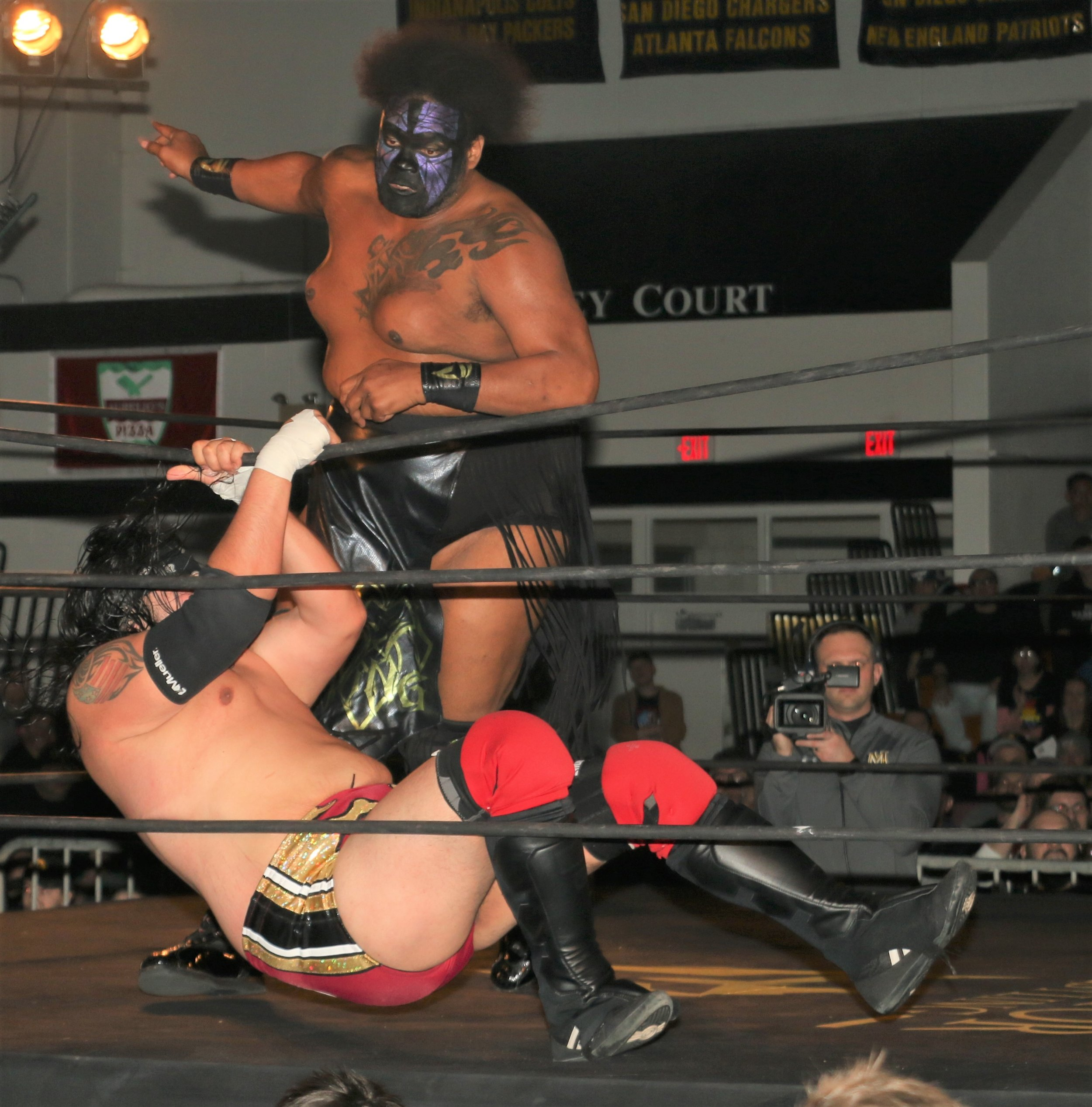 Chris Castro holds down the top rope, allowing Kongo Kong to fall to the floor during the three-way tag team match.
