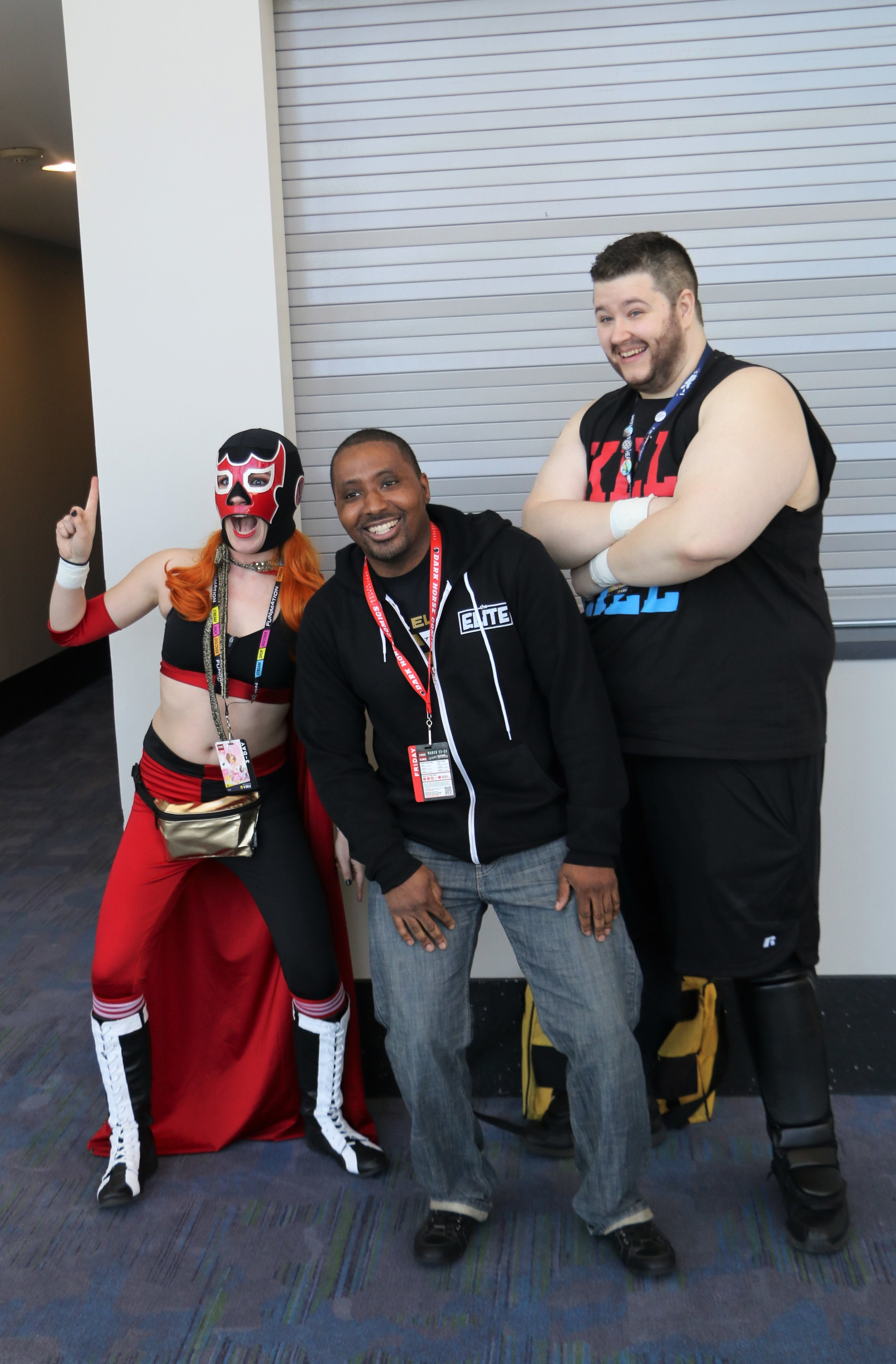 A fan poses with the El Generico and Kevin Steen cosplayers.