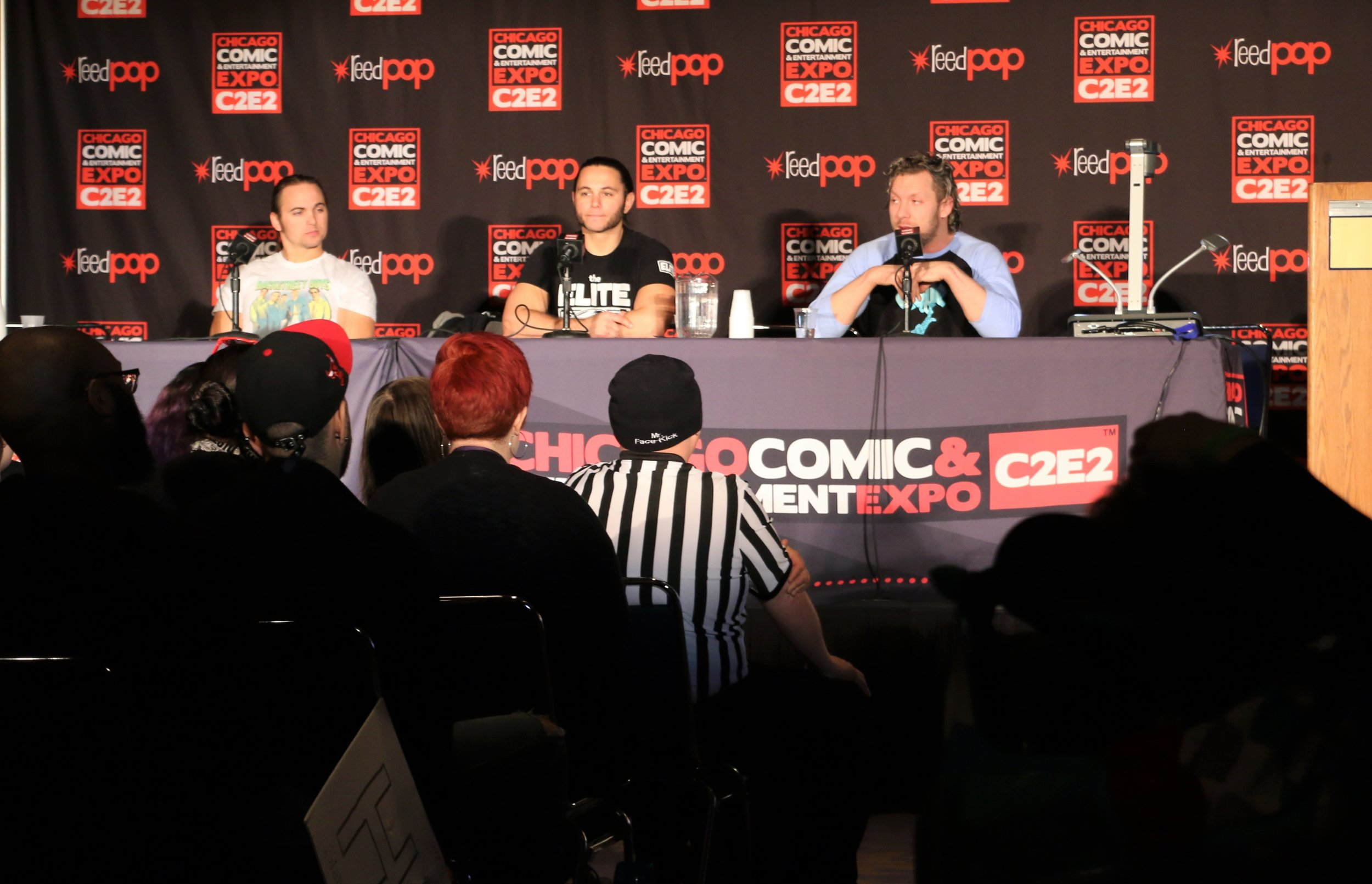 A packed conference room watches the Young Bucks and Kenny Omega during the All Elite Wrestling panel.