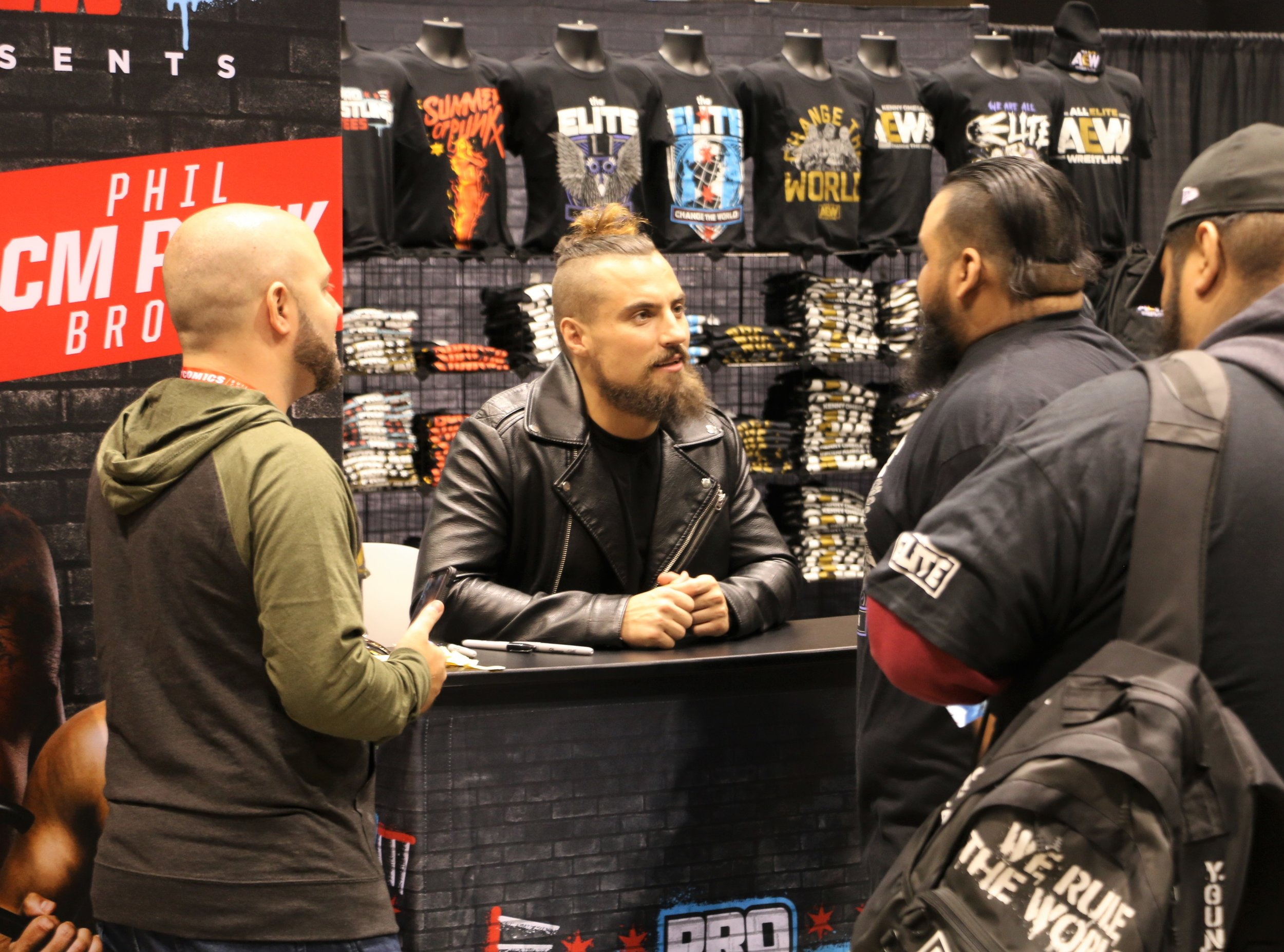 Ring of Honor star Marty Scurll, center, talks with fans at the Pro Wrestling Tees booth.