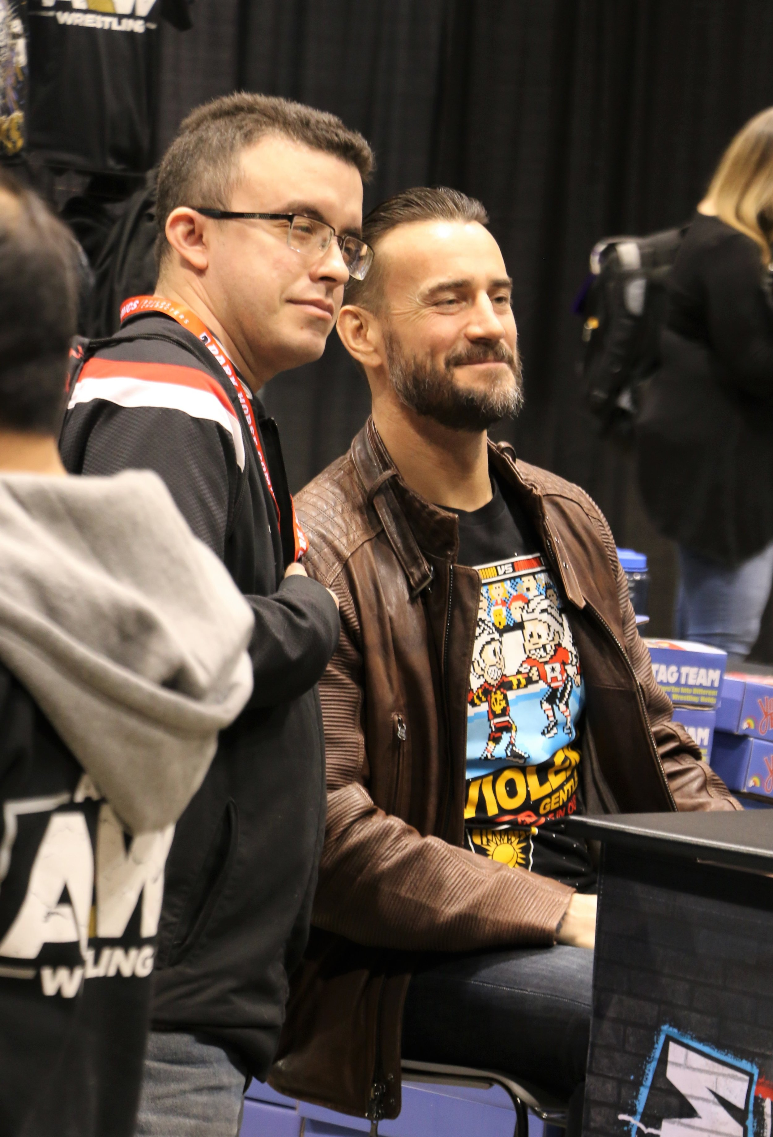 CM Punk, right, poses with a fan at the Pro Wrestling Tees booth.