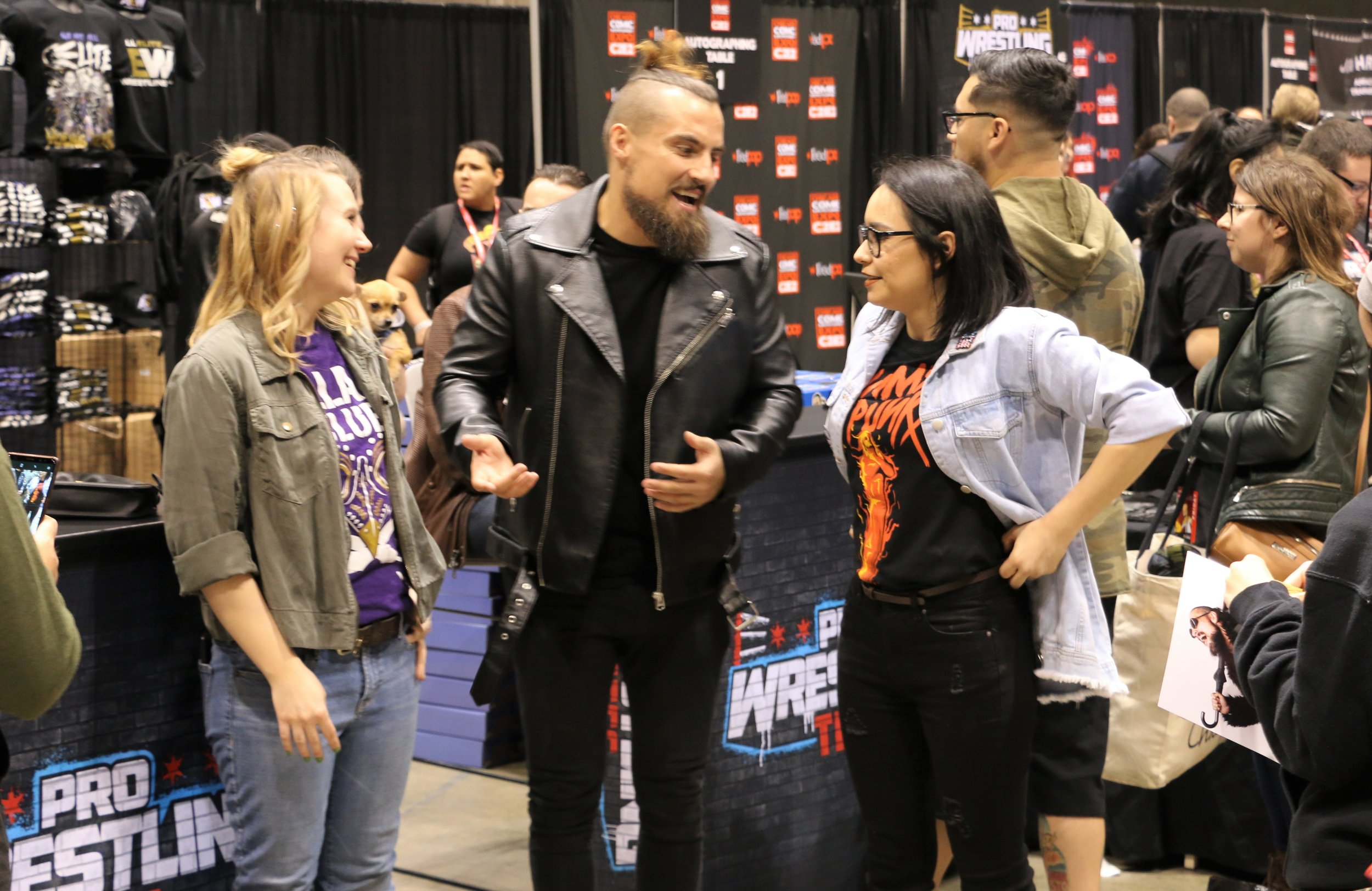 ROH star Marty Scurll, center, talks with fans at Pro Wrestling Tees booth.