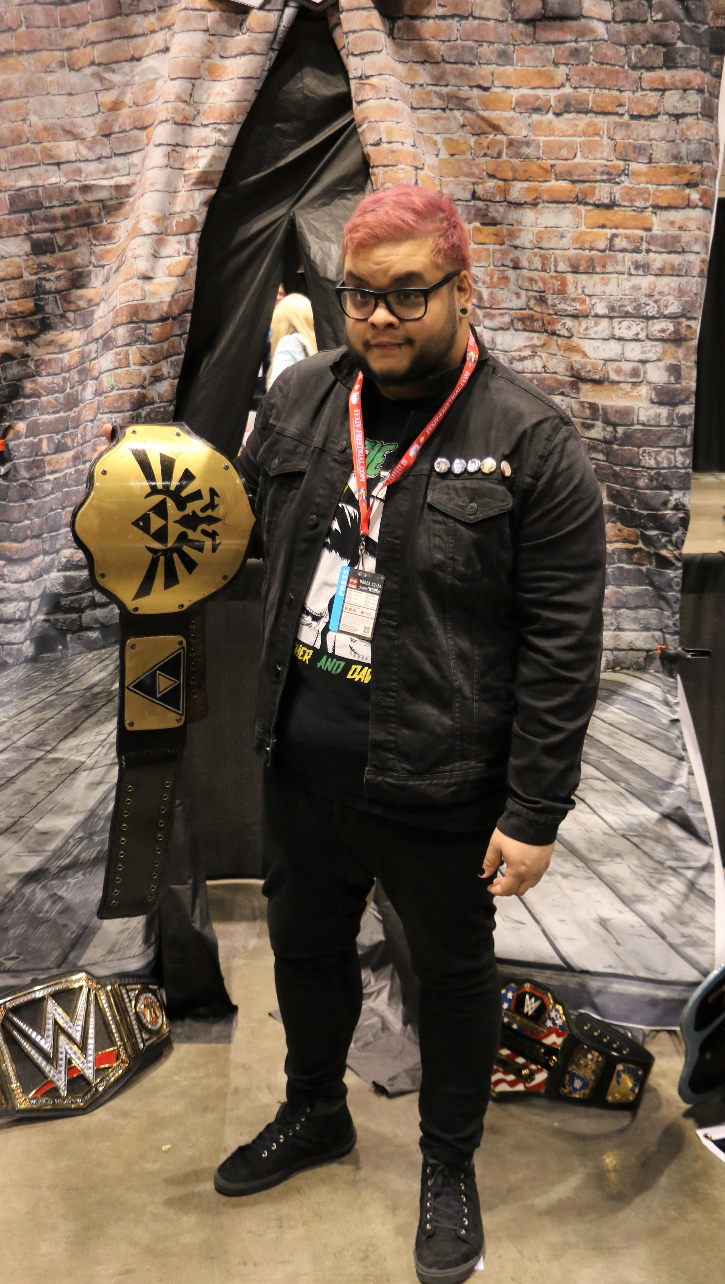 "A fan poses with the ""Triforce"" championship belt at the Too Sweet Cosplay booth."