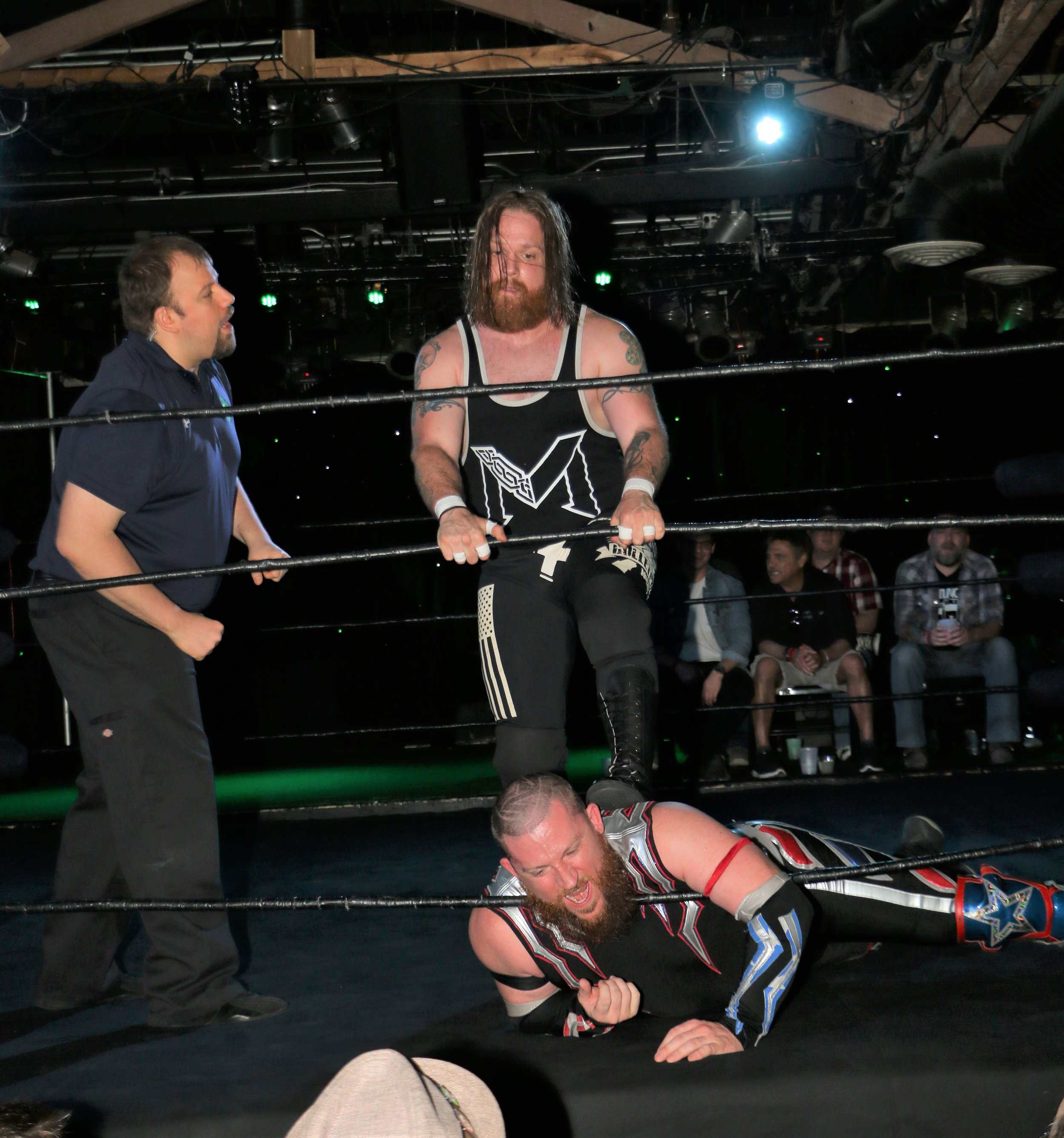 The referee warns Ben McCoy, who choking Gringo Loco on the bottom rope.