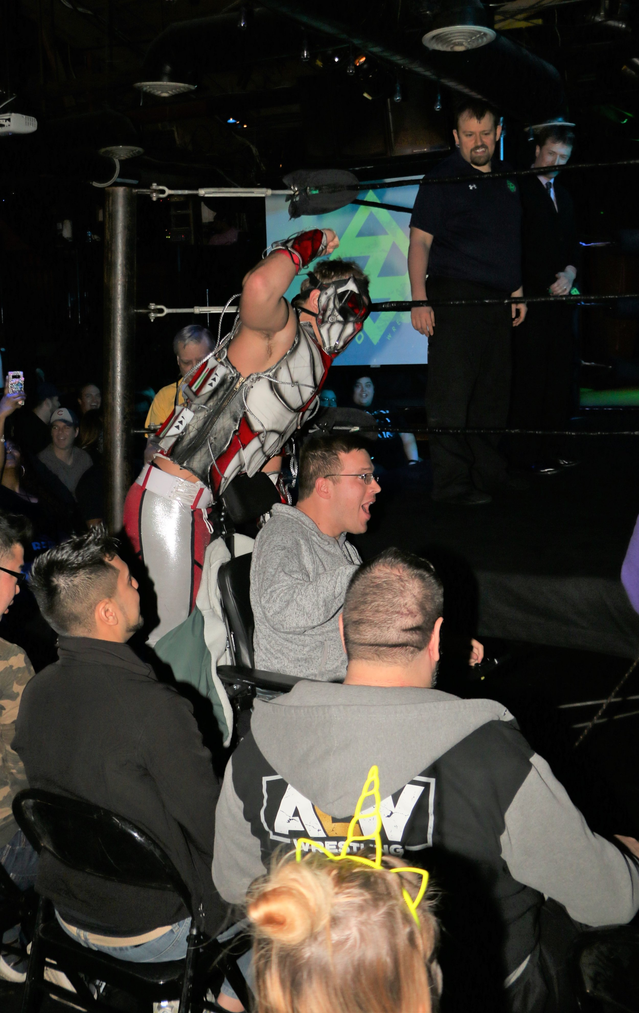 Pat Monix takes a ride on the back on a fan's wheelchair at ringside.