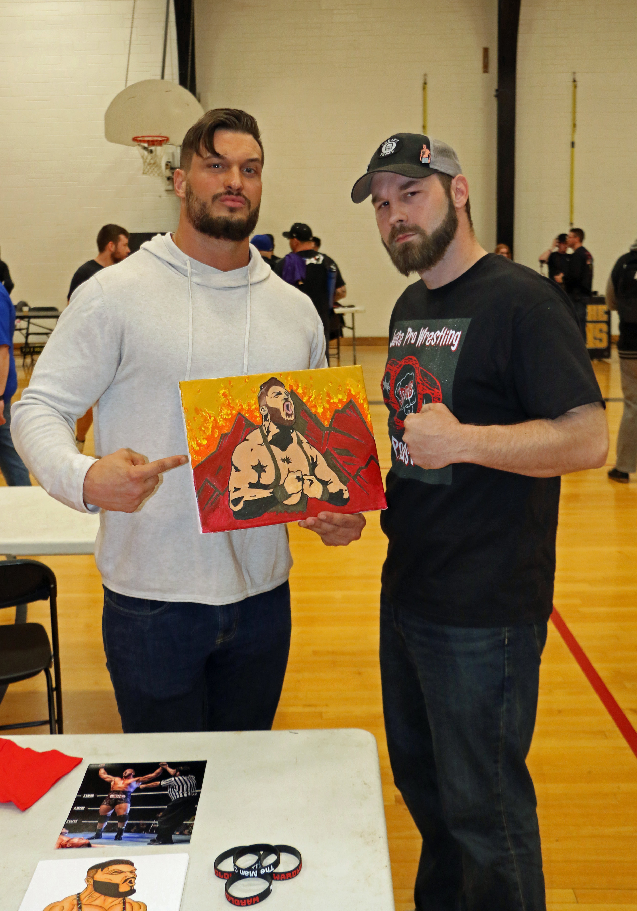 Wardlow poses with J.R. (and his artwork) from the Juice Pro Wrestling Podcast during the Warrior Wrestling 5 VIP Fan Fest.