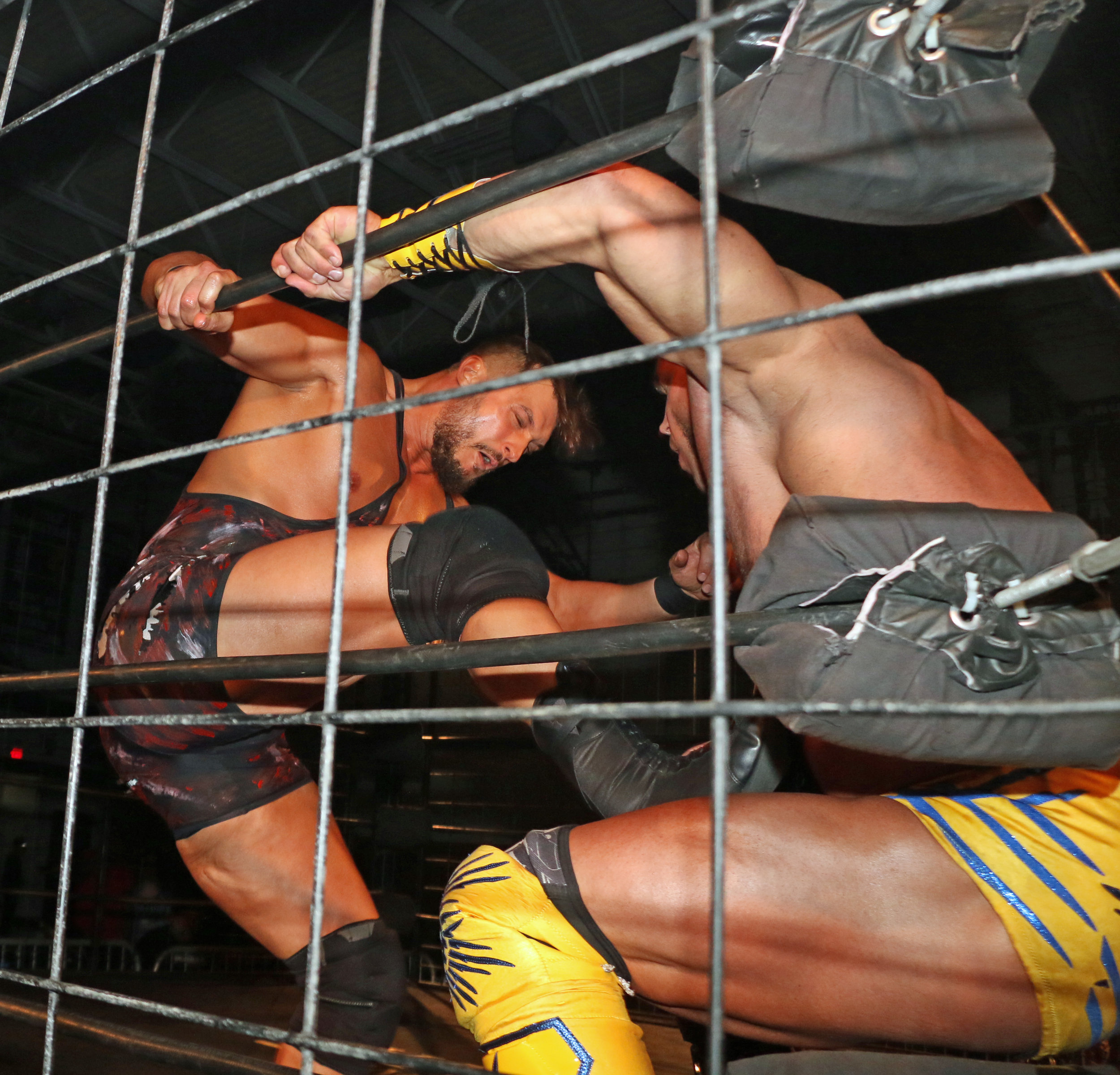 Wardlow stomps Brian Cage in the corner during the three-way cage match for the Warrior Wrestling Championship.