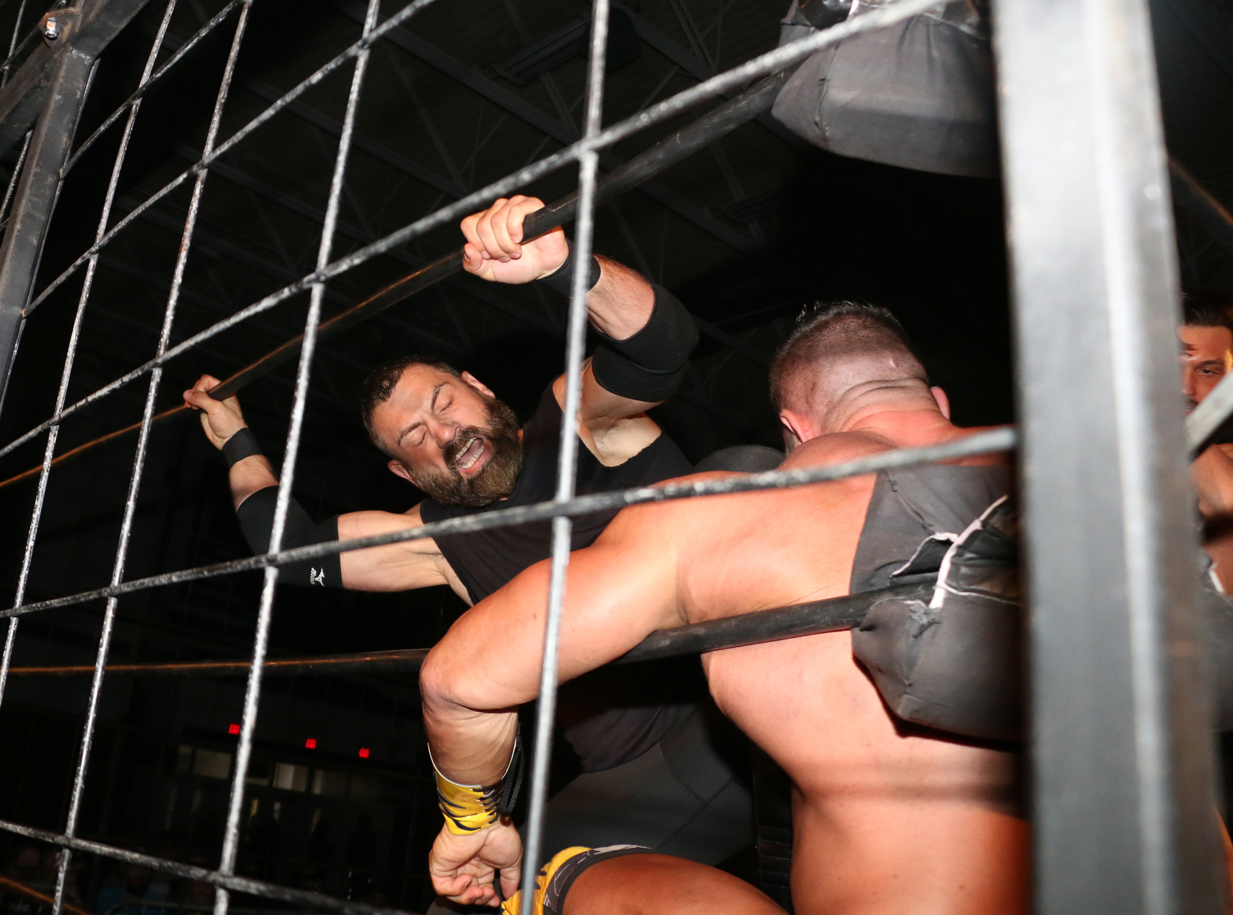 Austin Aries kicks Brian Cage in the corner during the three-way cage match for the Warrior Wrestling Championship.