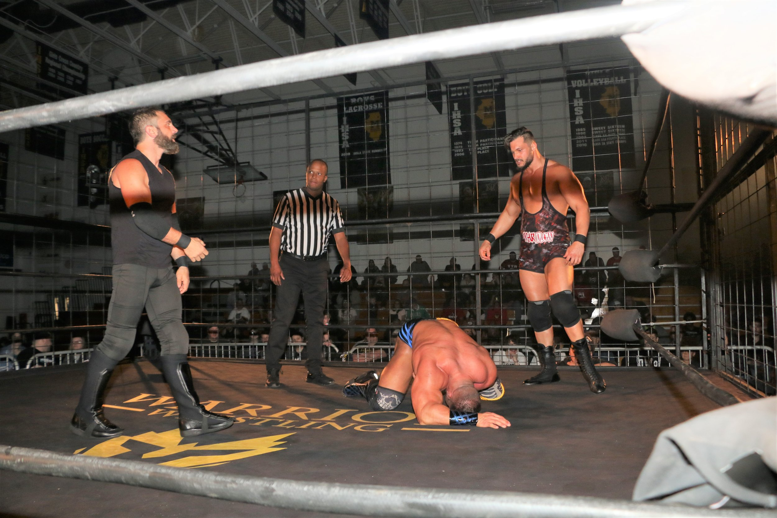 Austin Aries, left, and Wardlow, right, contemplate their next double-team move on Brian Cage.