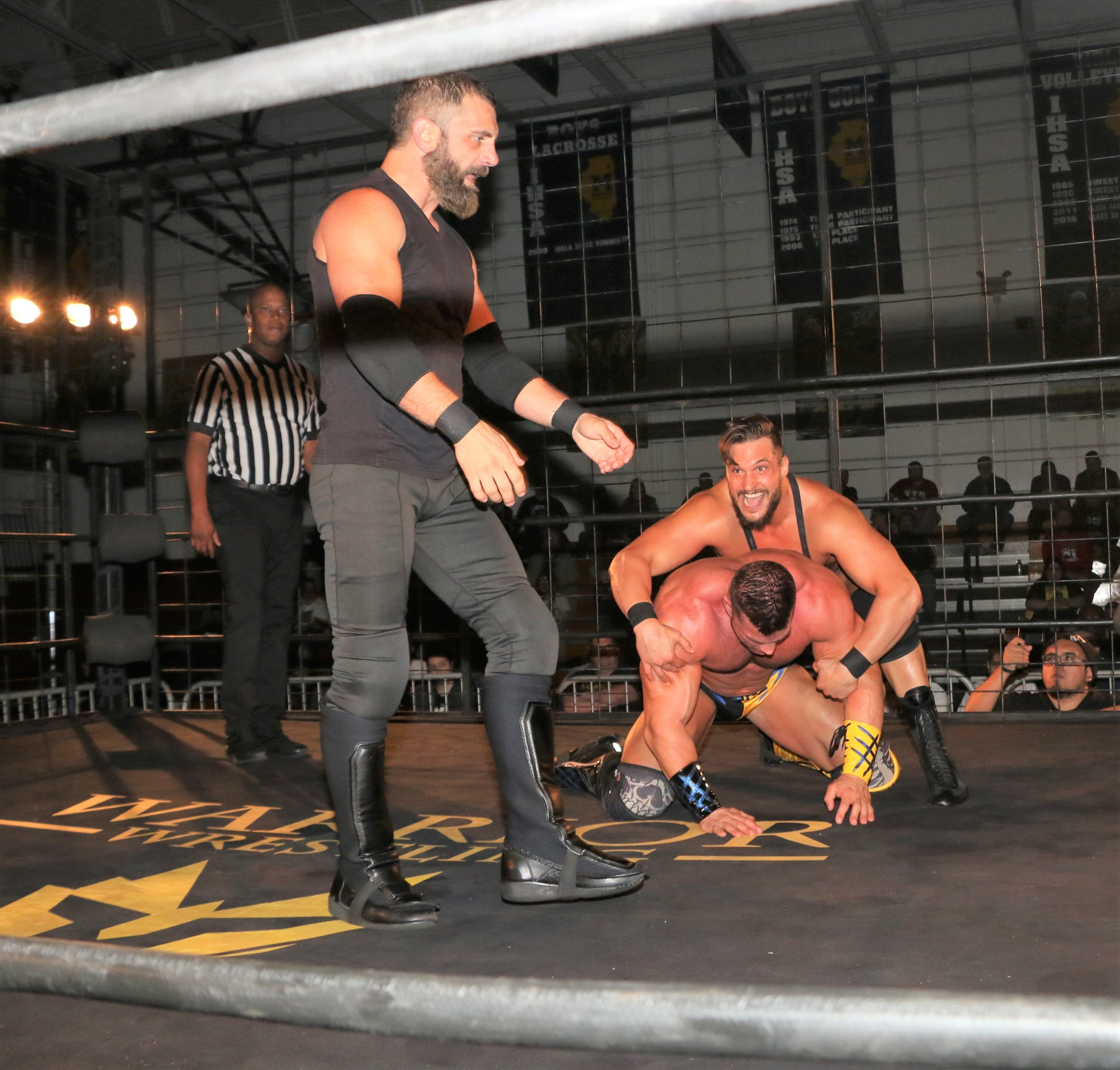 Wardlow holds Brian Cage, waiting for Austin Aries to deliver a blow.
