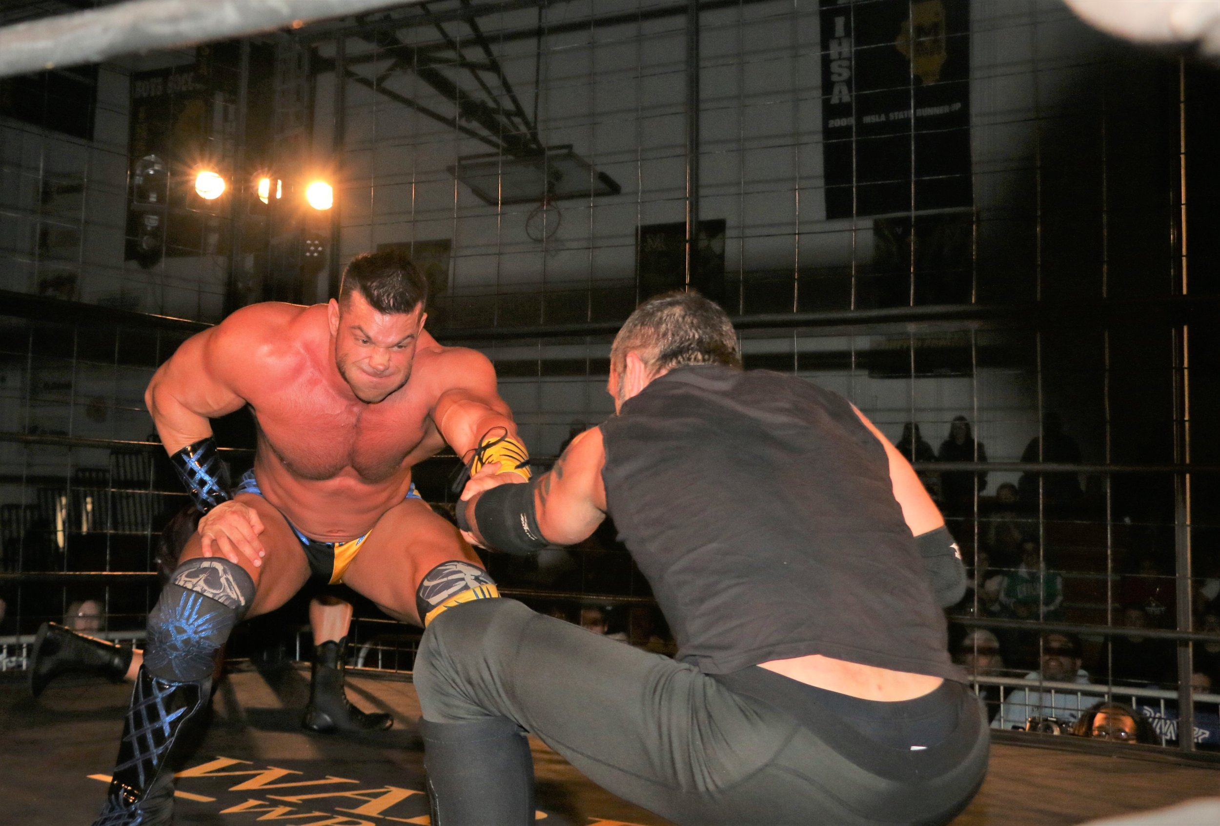 Brian Cage prevents Austin Aries from whipping him into the corner.
