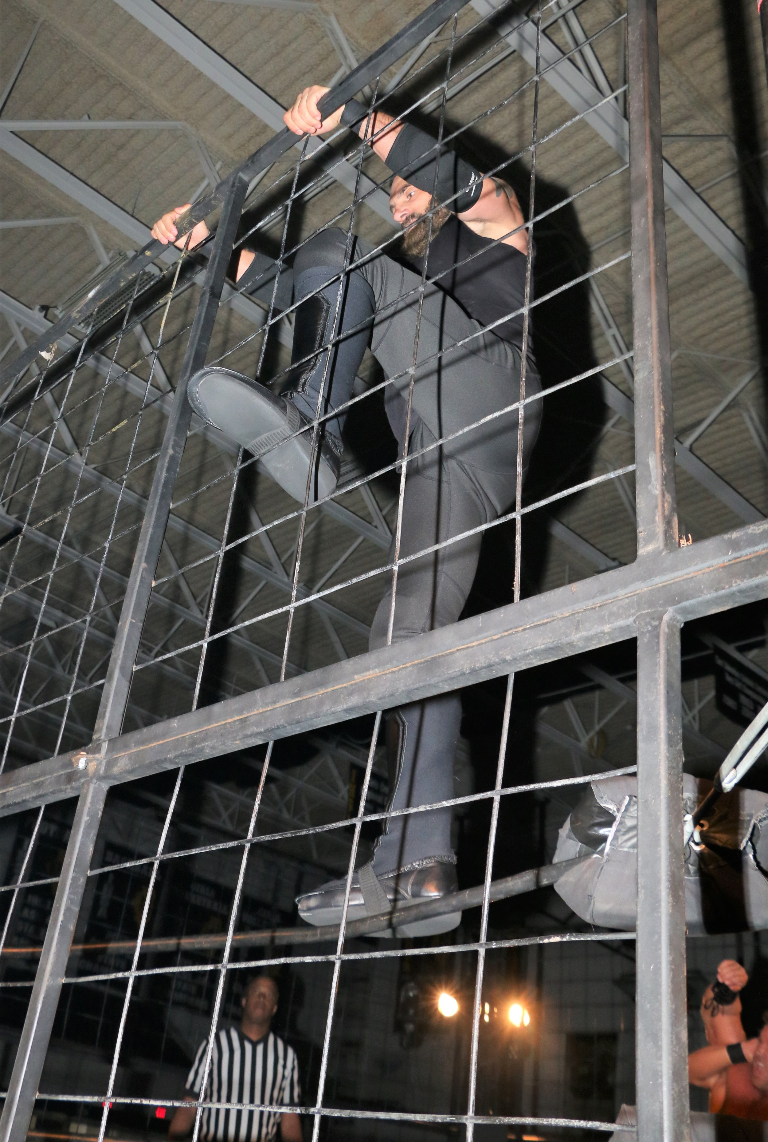 Austin Aries tries to escape the cage.