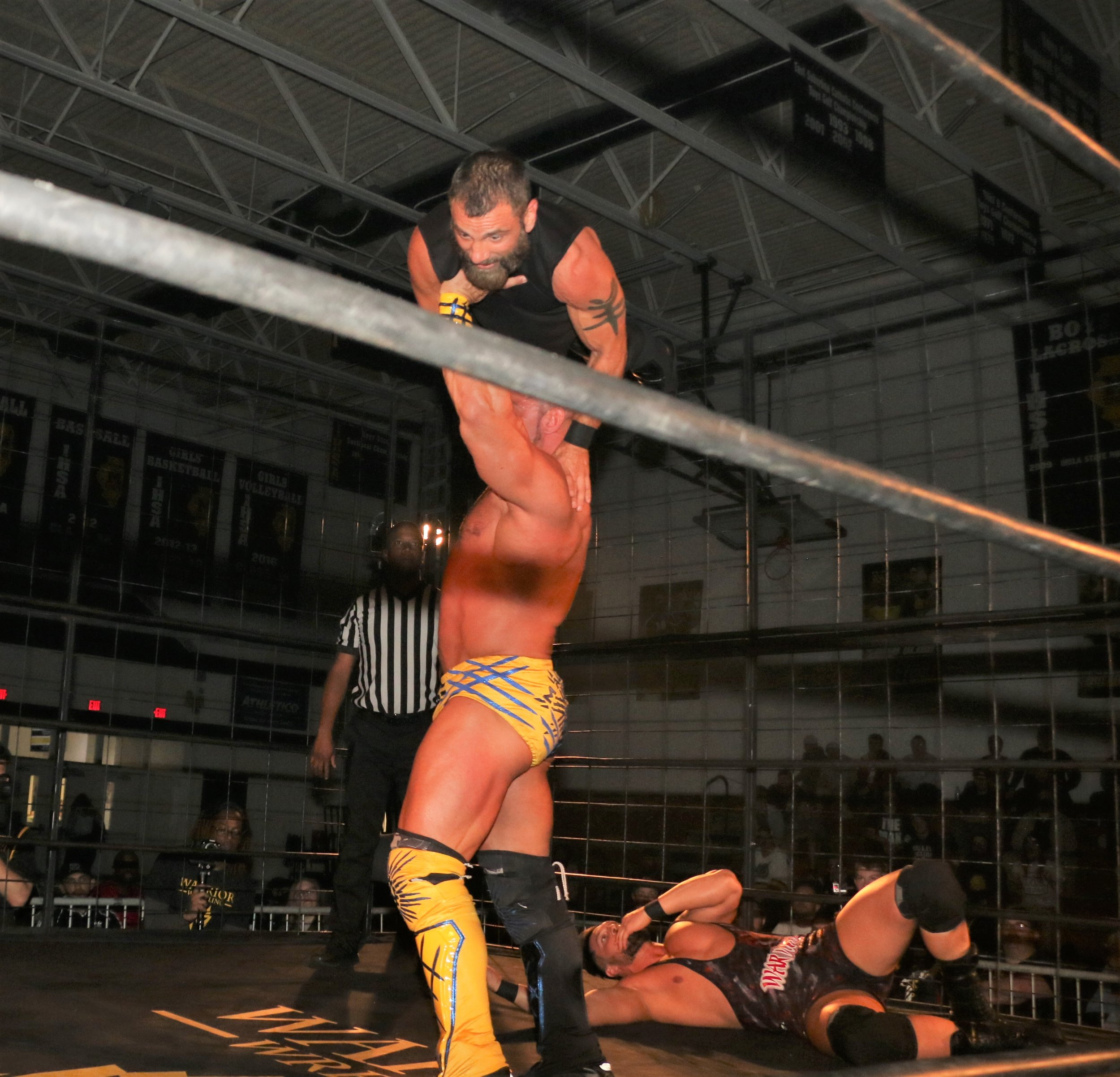 Brian Cage hoists Austin Aries up in a gorilla press.