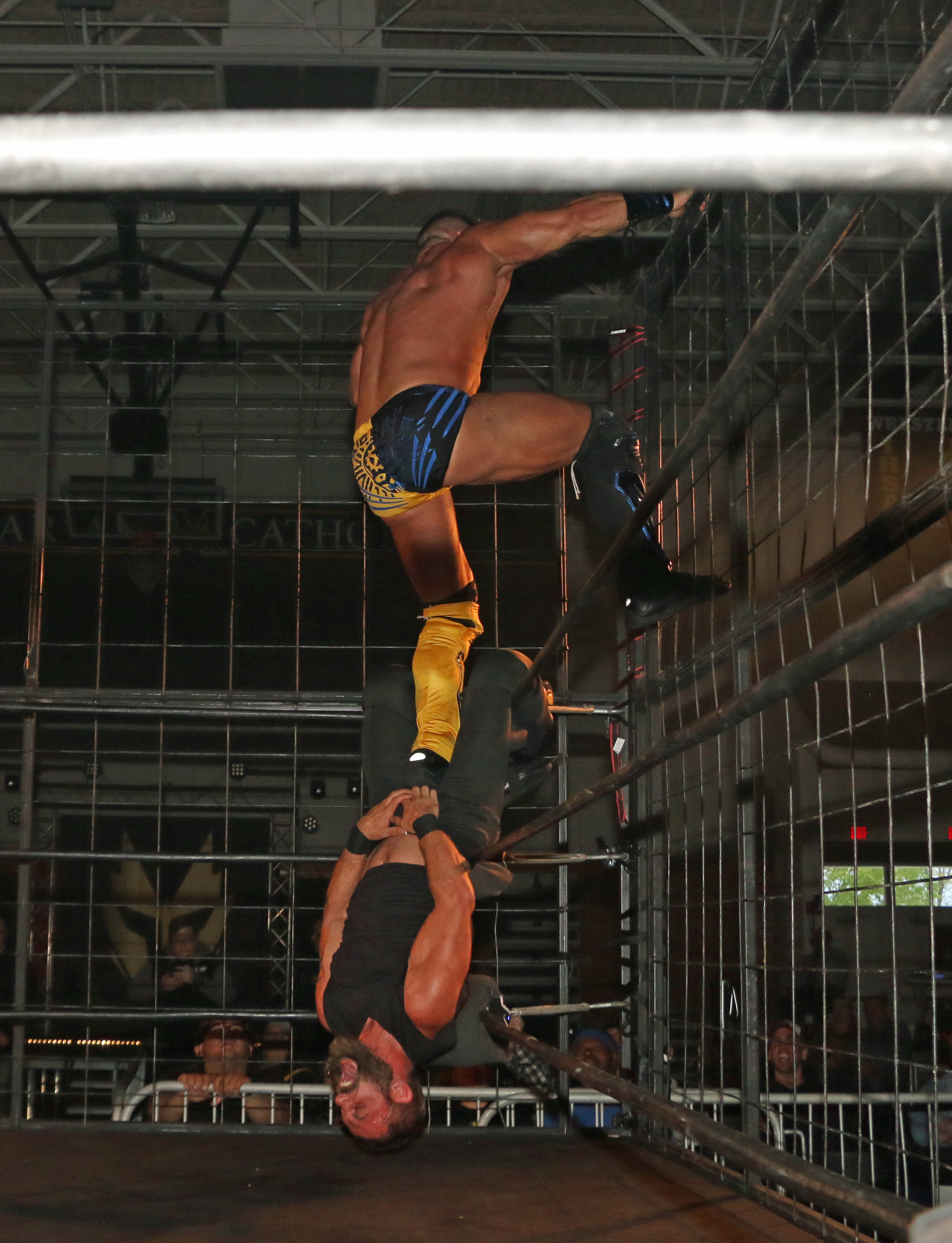 Brian Cage stomps on Austin Aries' crotch as he climbs the side of the cage.