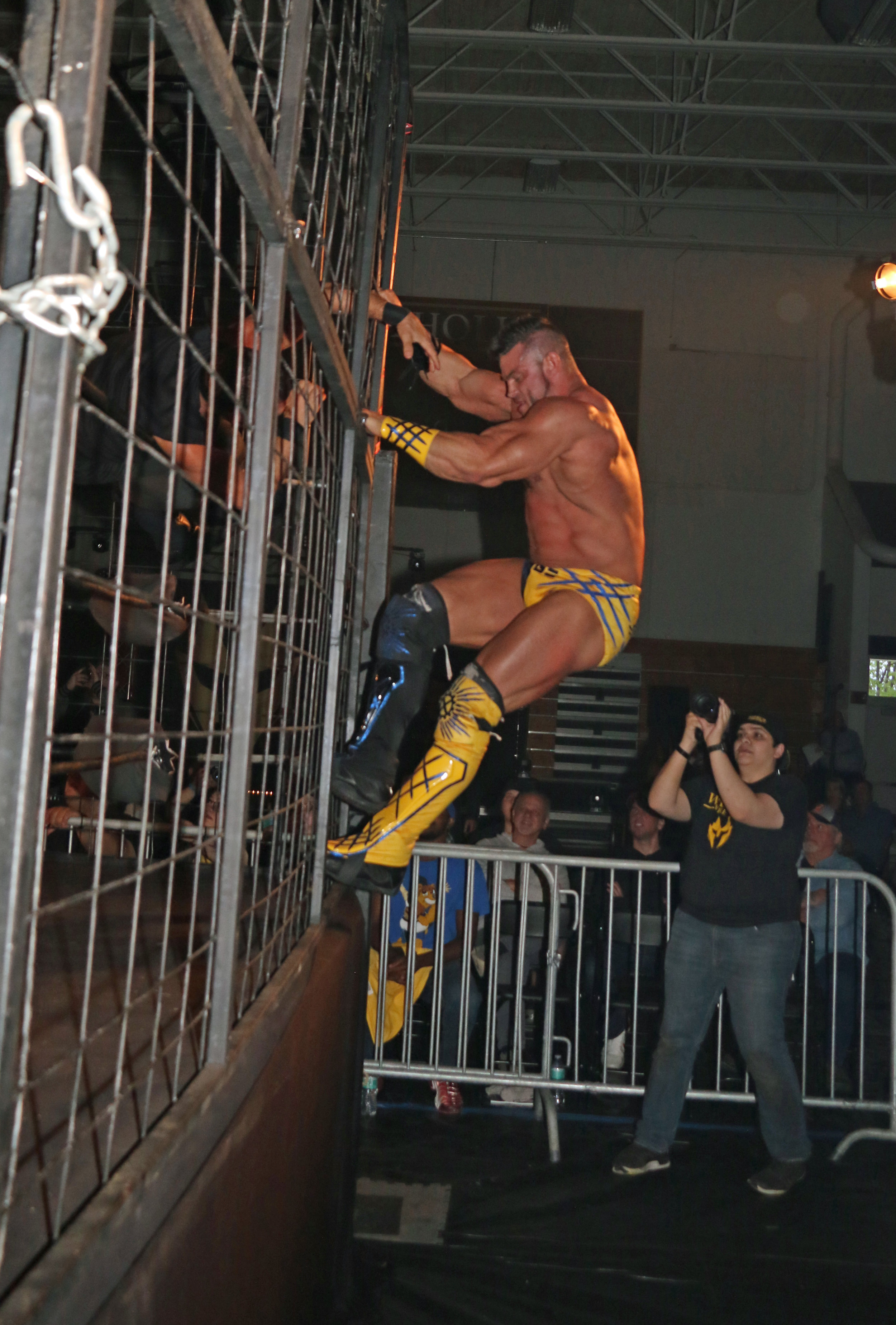 Brian Cage climbs down the cage toward victory.