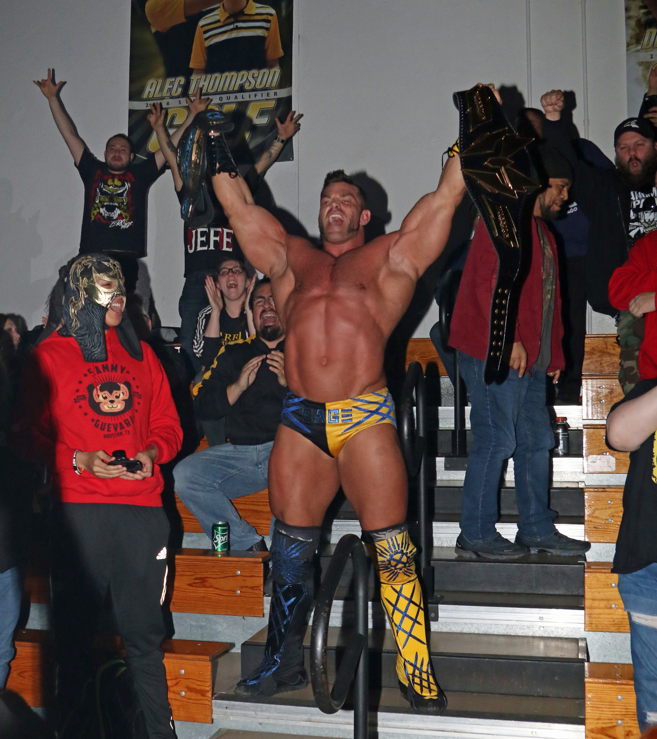 Brian Cage raises both of his titles as he celebrates in the bleachers with the fans.