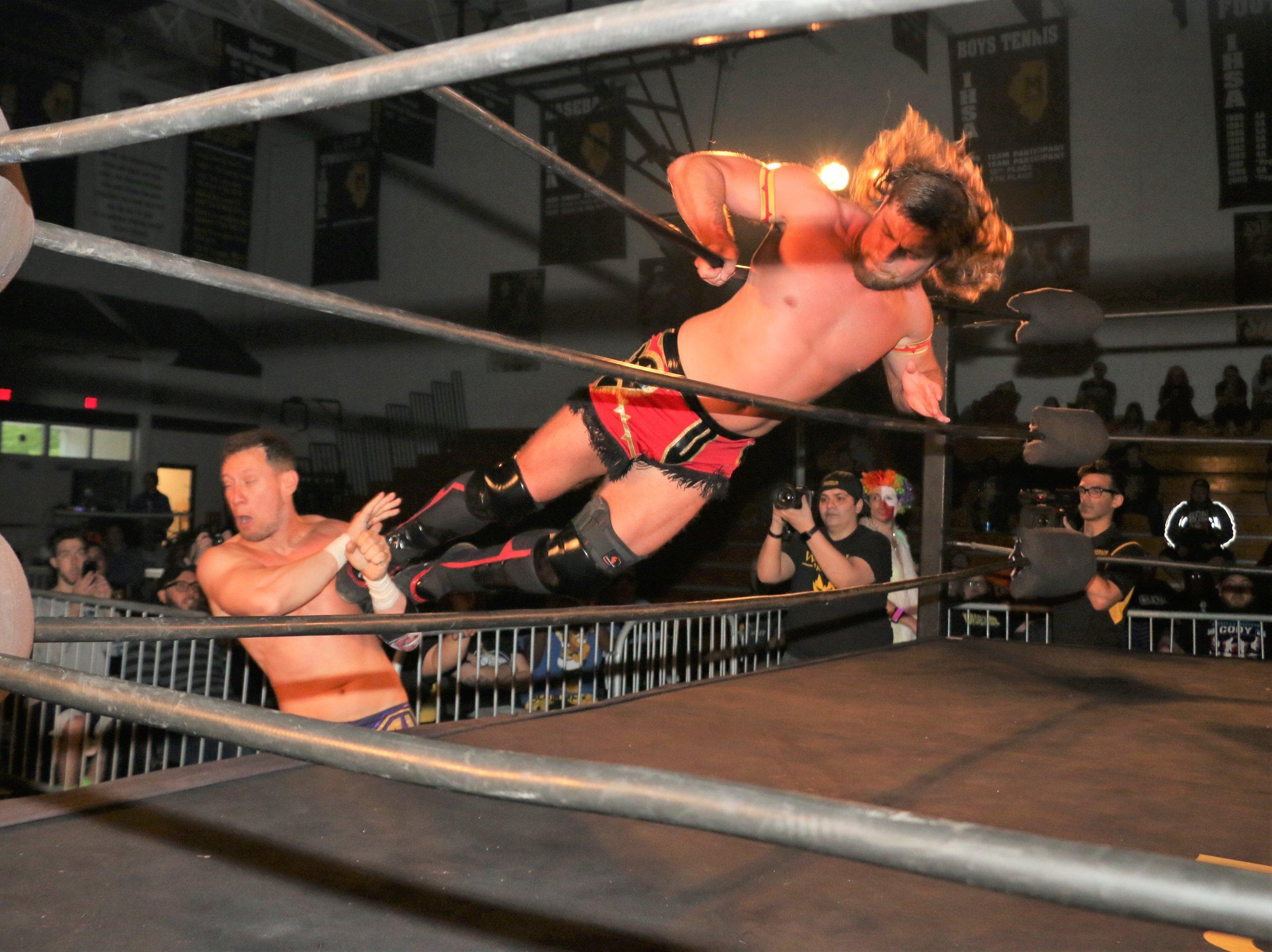 "Brian Pillman Jr. drop kicks Robert ""Ego"" Anthony through the ropes."