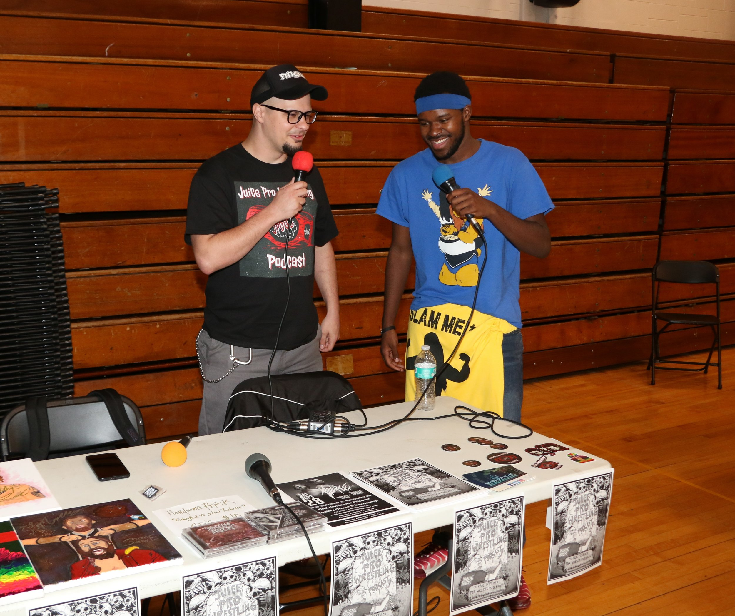 Juice talks to a fan at the Juice Pro Wrestling Podcast table during intermission.