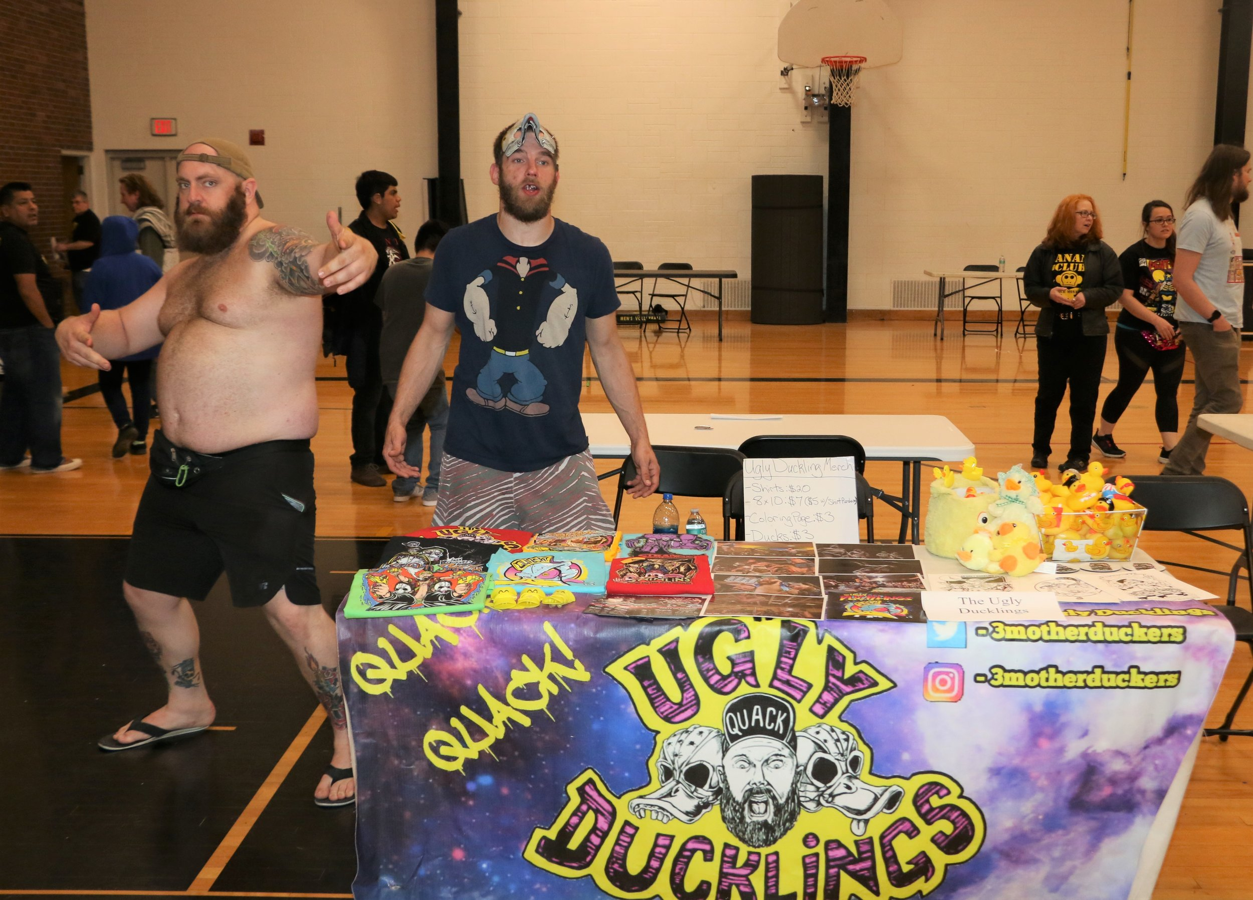 The Ugly Duckings man their merchandise table during intermission.