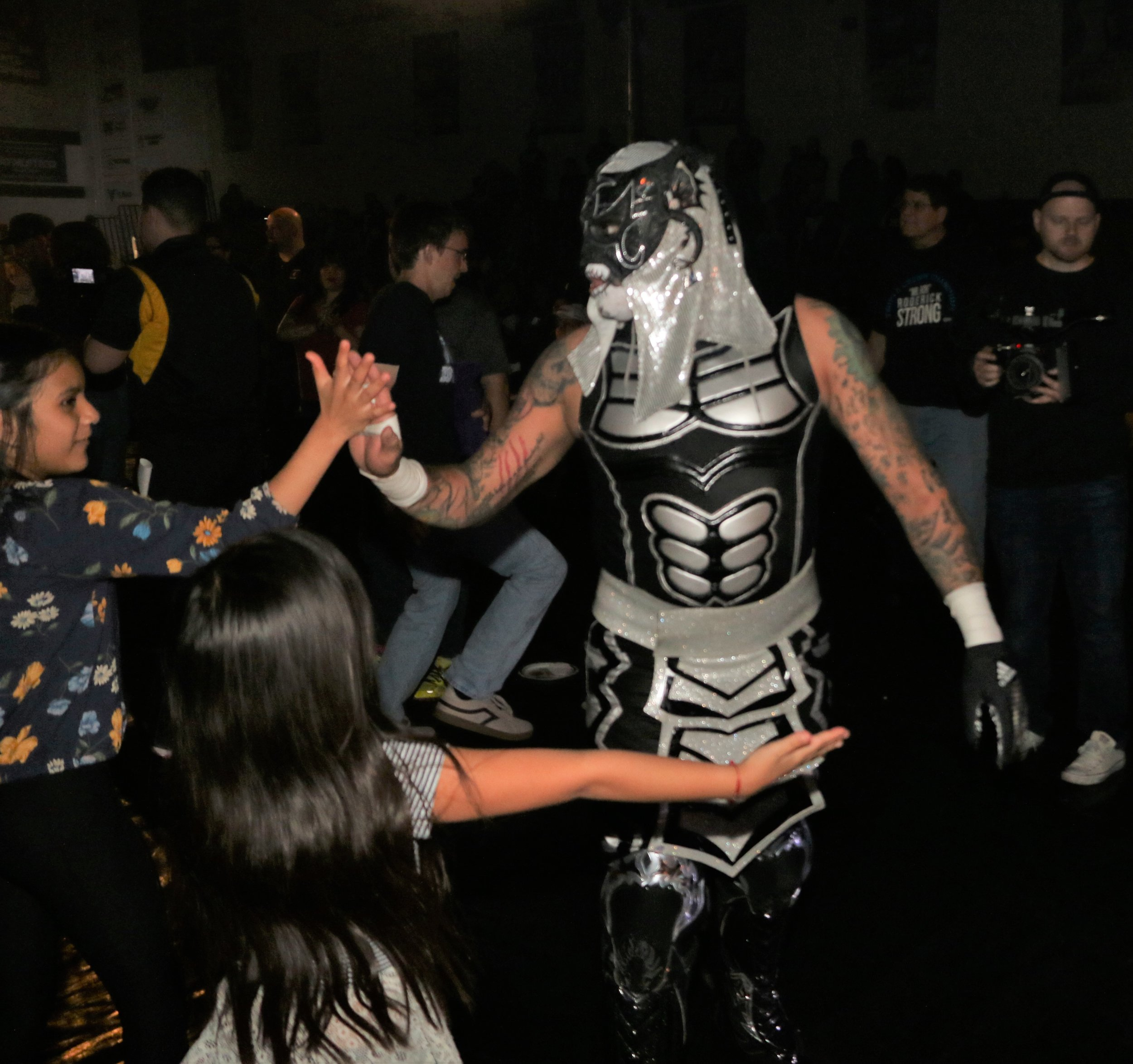 Penta El 0M celebrates with fans after the Lucha Bros. victory over Daga and Kotto Brazil.