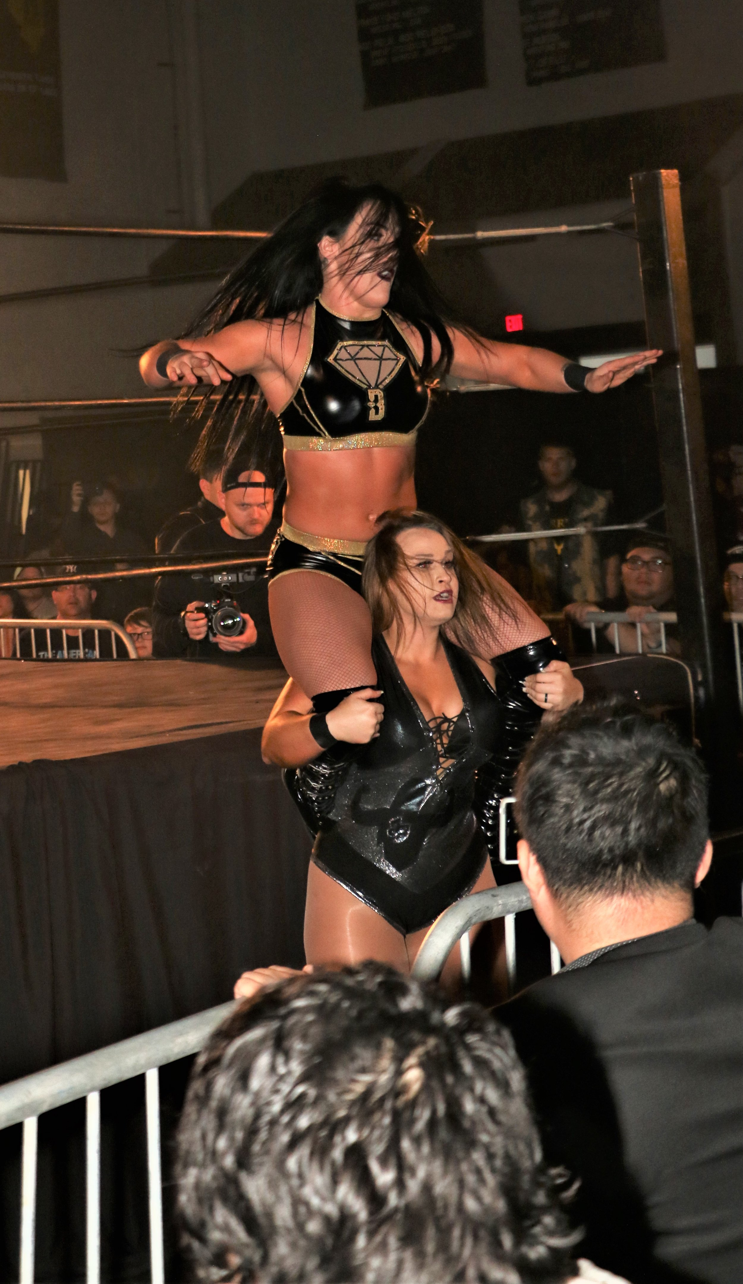 Jordynne Grace holds Tessa Blanchard up on her shoulders on the outside of the ring.