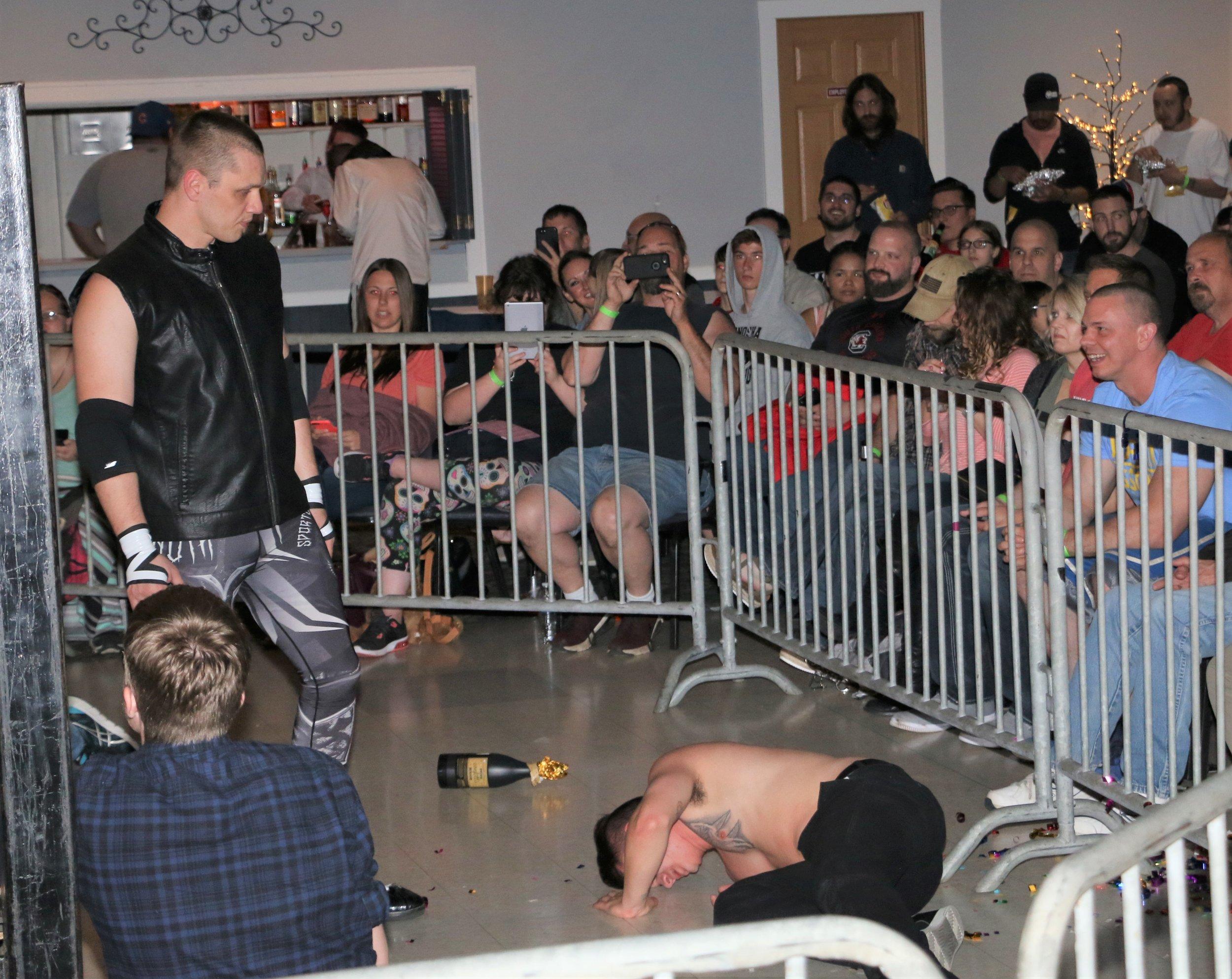 John Fate, left, looks over Junior Jangles on the floor outside the ring.