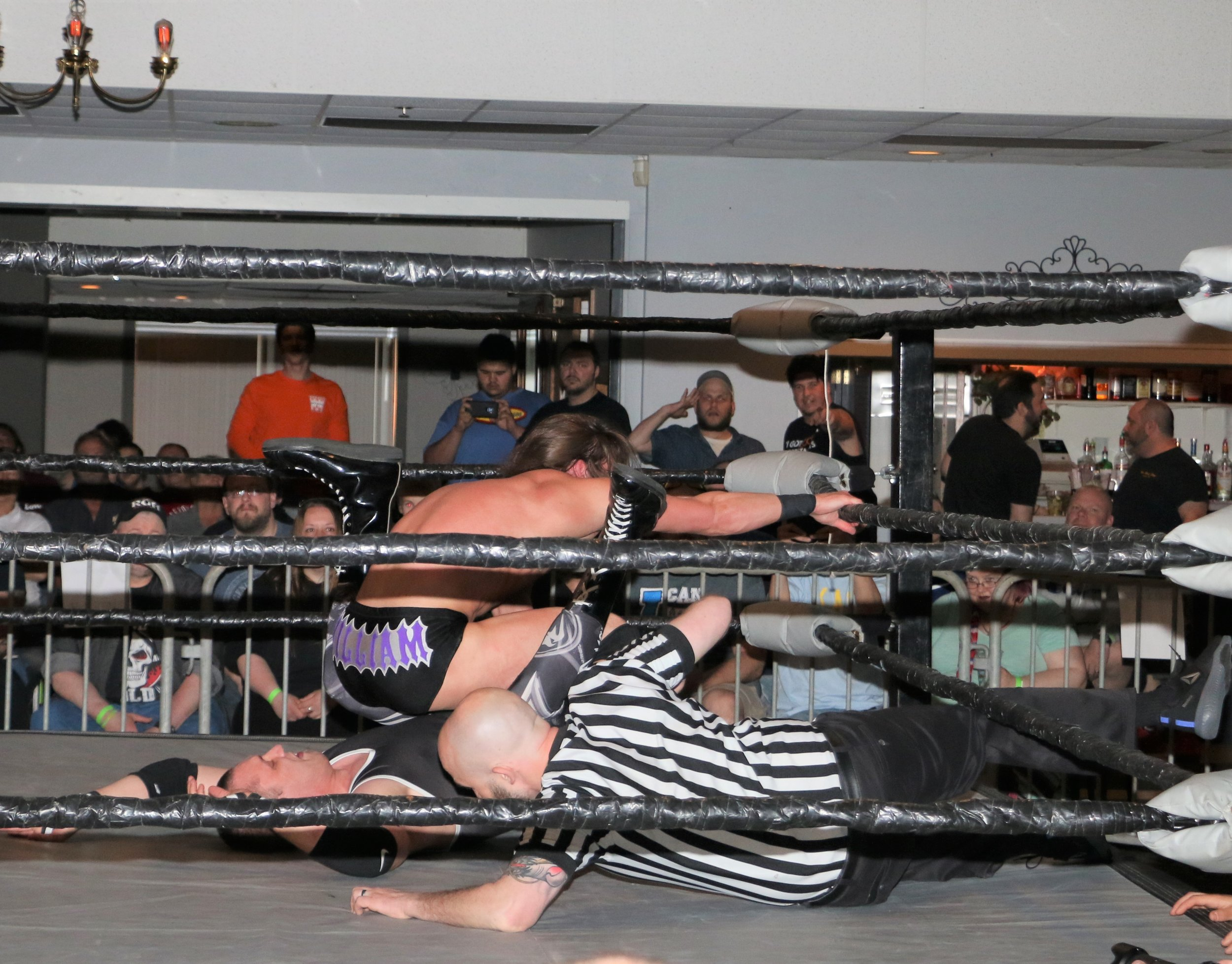William Jacobs attempts to pin John Fate while holding the ropes for leverage.