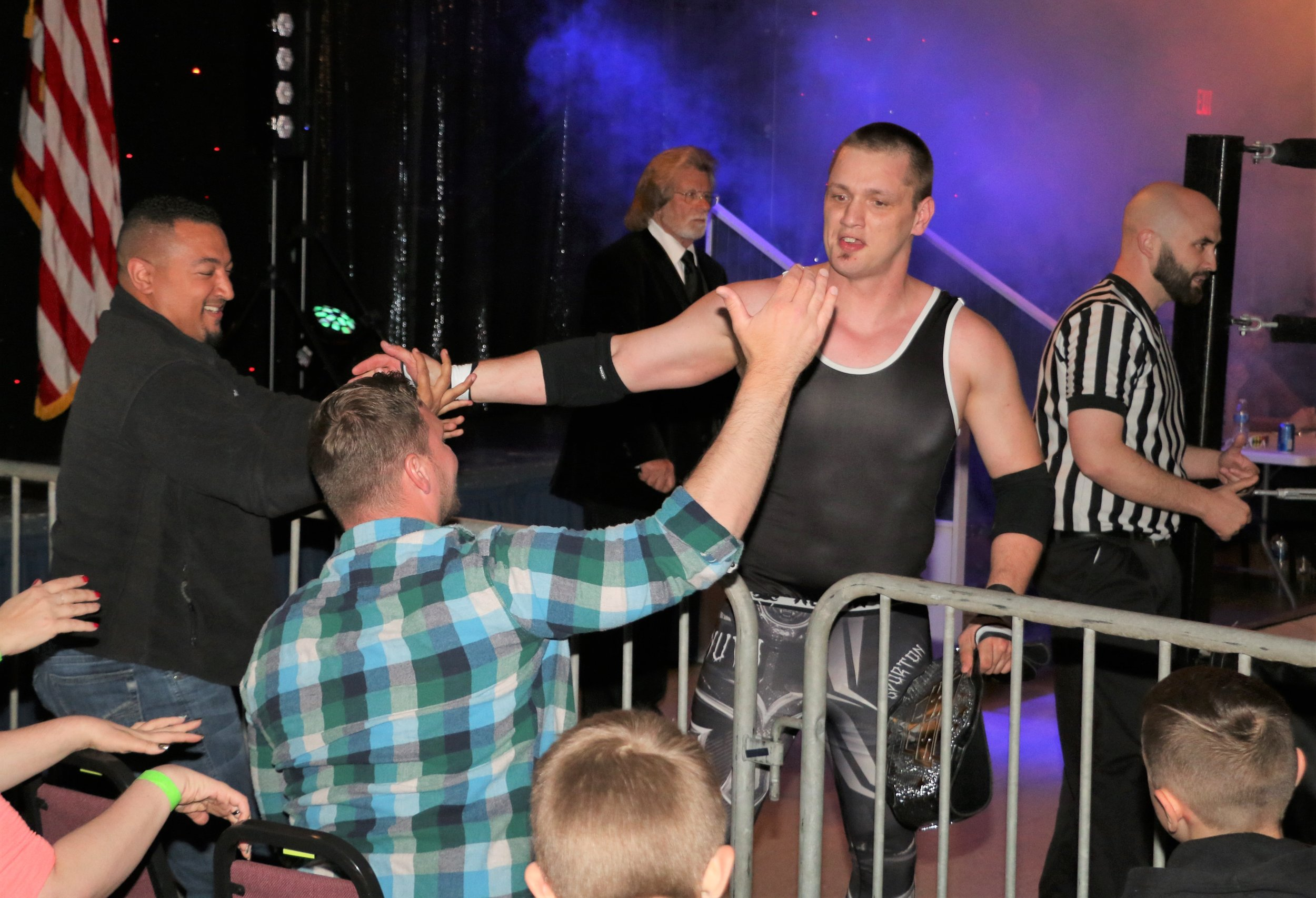 New SSW Champion John Fate celebrates with ringside fans.