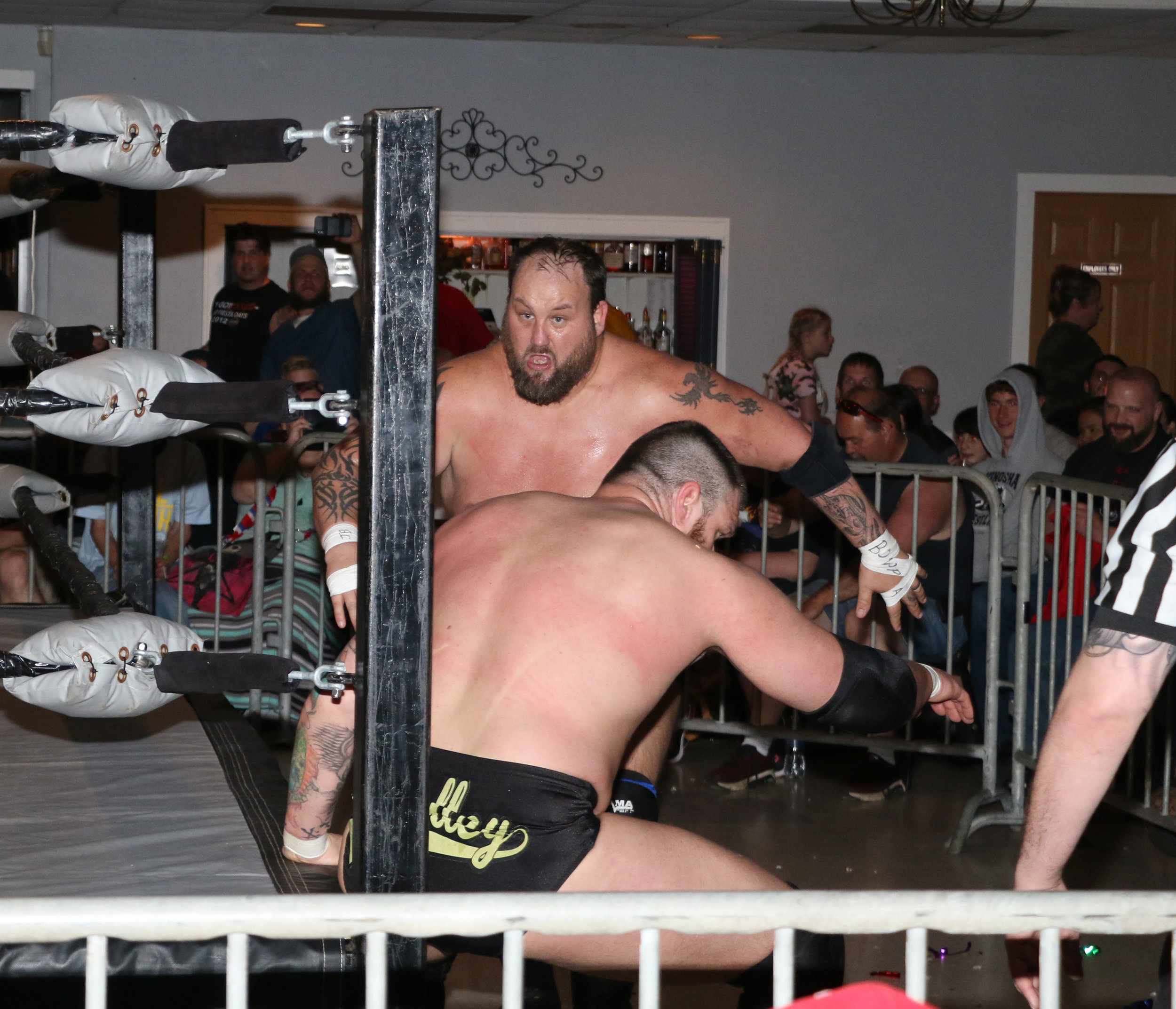 Beer City Bruiser charges at Jay Bradley outside the ring.