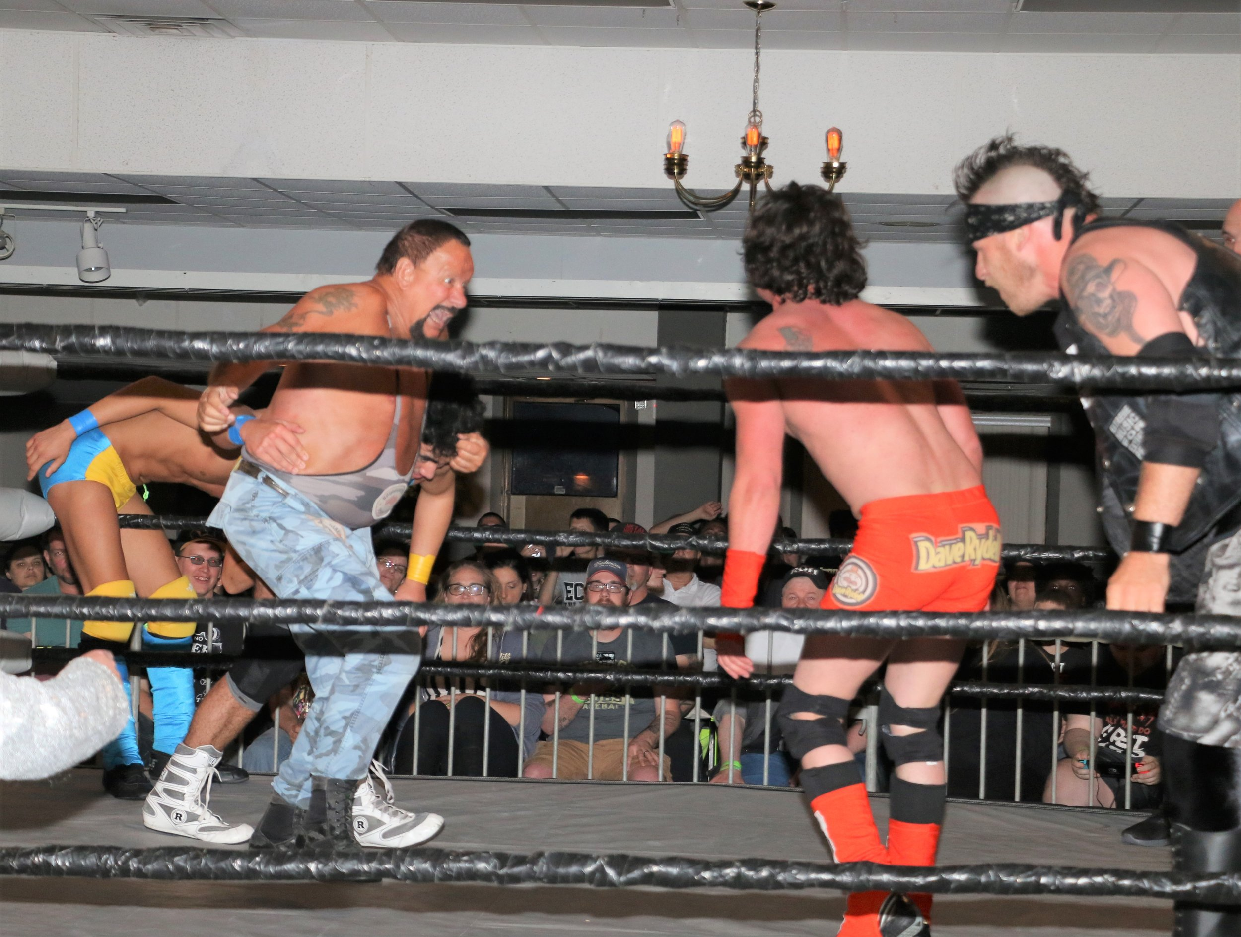 Bushwhacker Luke looks to deliver the battering ram to Dave Rydell during the six-man tag team match.