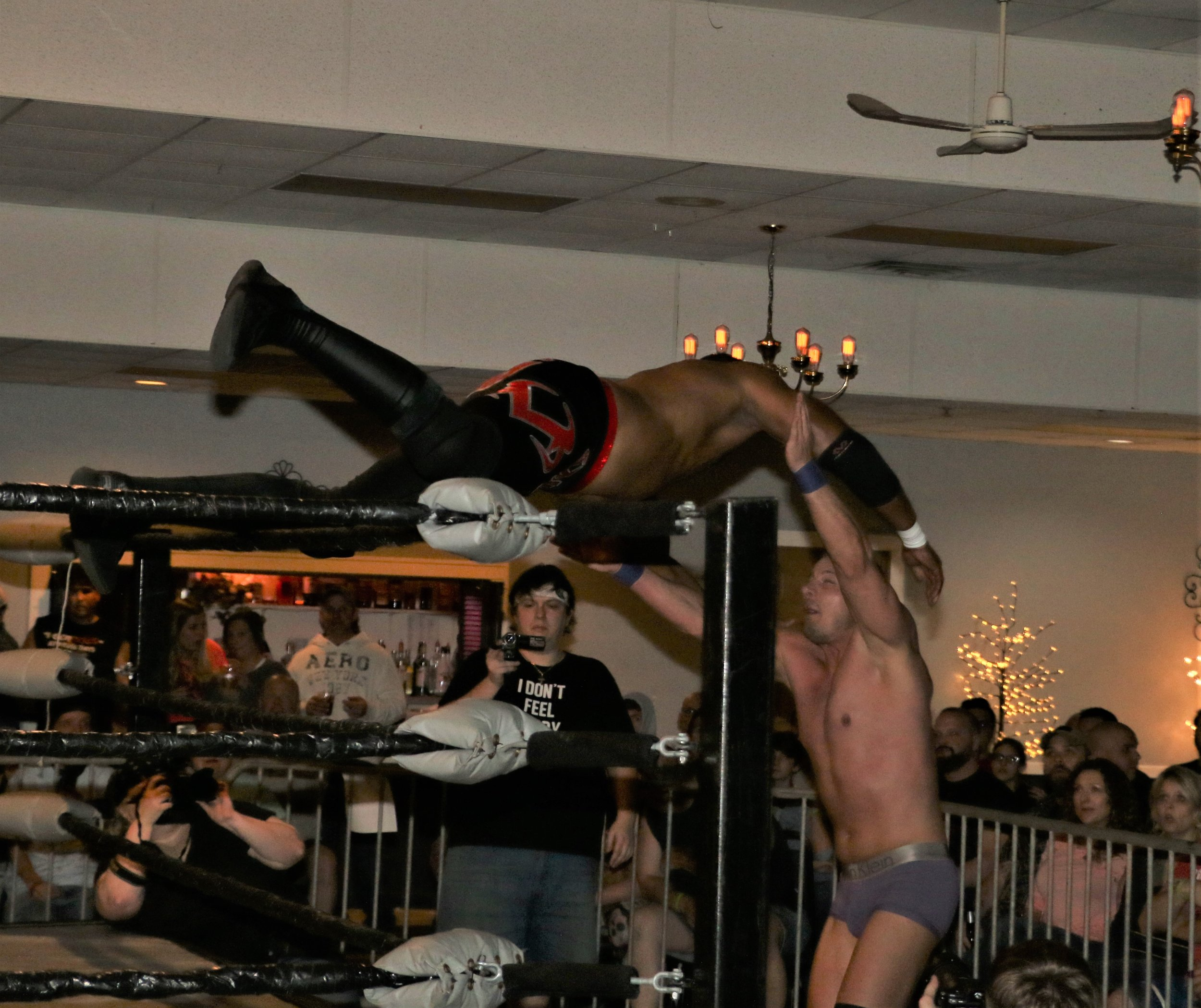 Marshe Rockett dives over the ropes onto Eric Priest.